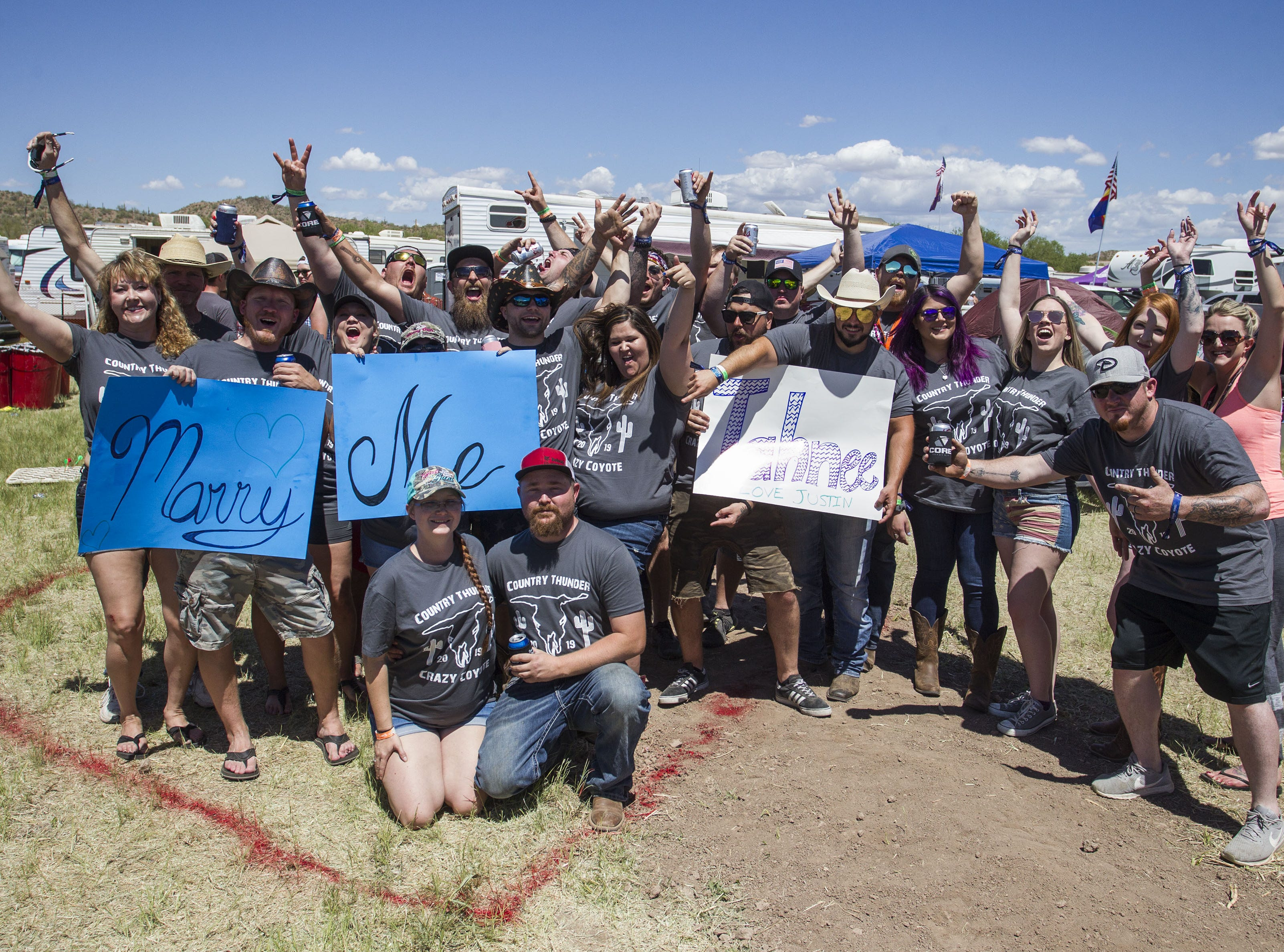 Friends of the Crazy Coyote Camp celebrate the marriage proposal of Tahnee Billingsly and Justin Adams during Country Thunder Arizona Saturday, April 13, 2019, in Florence, Arizona.