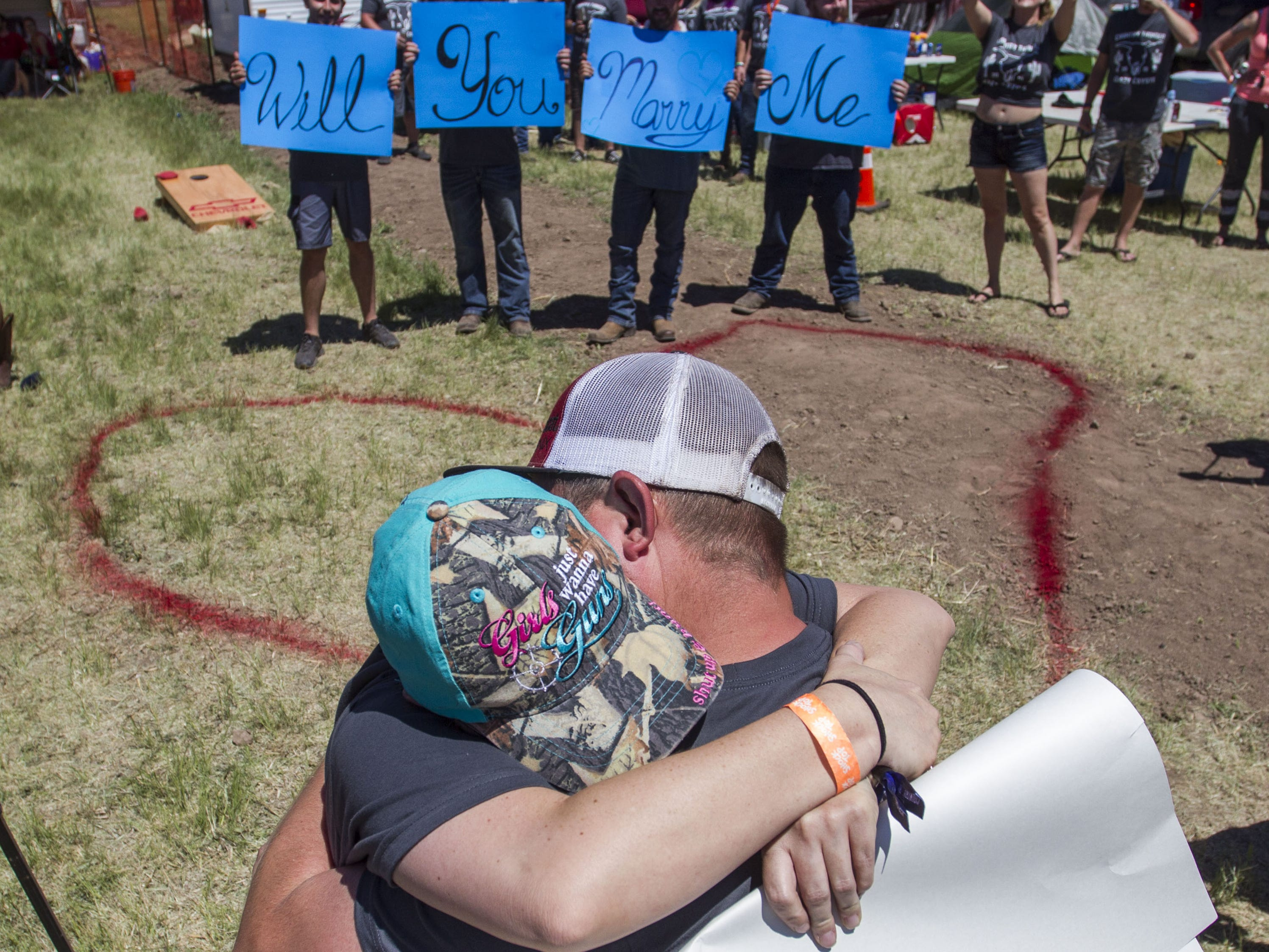 Tahnee Billingsly and Justin Adams hug after she accepted his marriage proposal during Country Thunder Arizona Saturday, April 13, 2019, in Florence, Ariz.