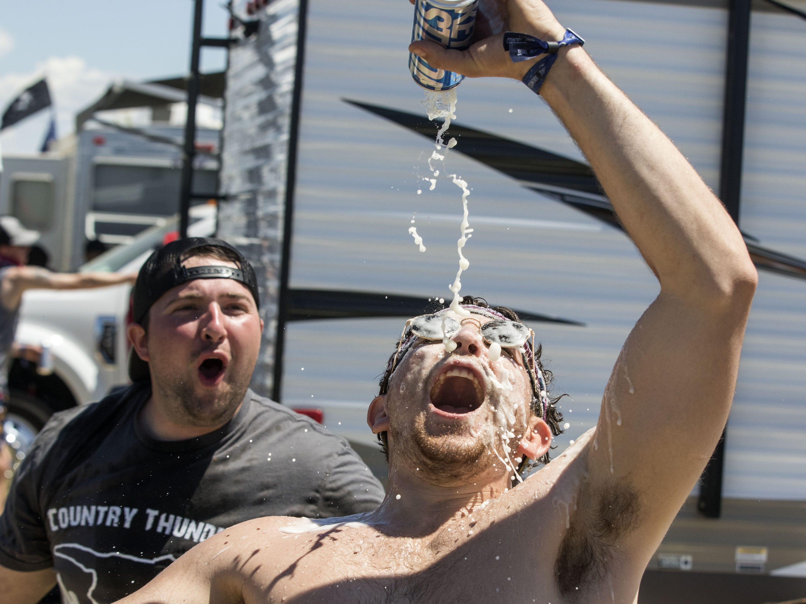 Brett Goetz of Phoenix watches as Coty Cruse of Flagstaff gives himself a beer shower during Country Thunder Arizona Friday, April 13, 2019, in Florence, Ariz.