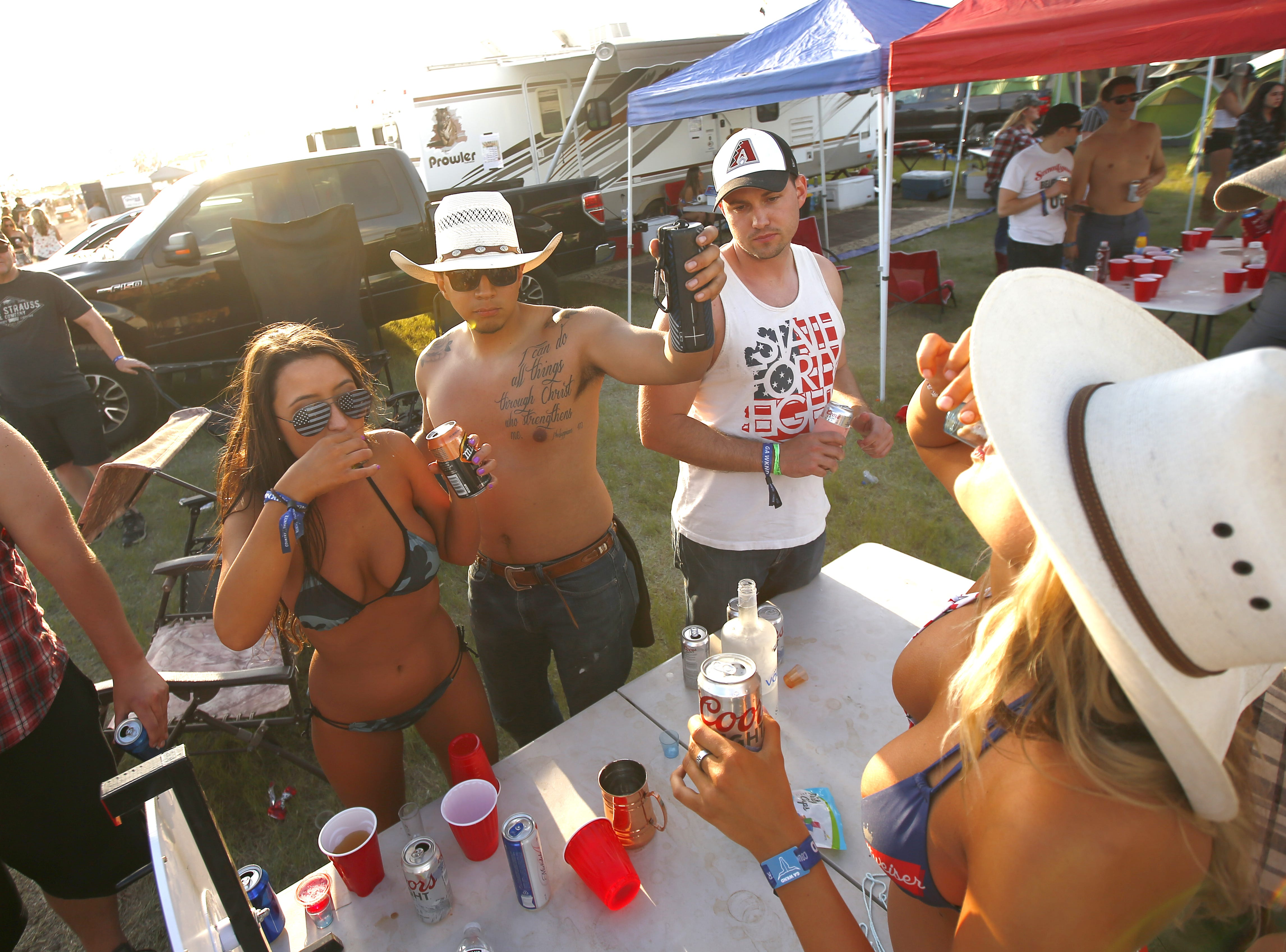 People gather for shots at the campsite Coyote during Country Thunder in Florence, Ariz. on Friday, April 12, 2019.