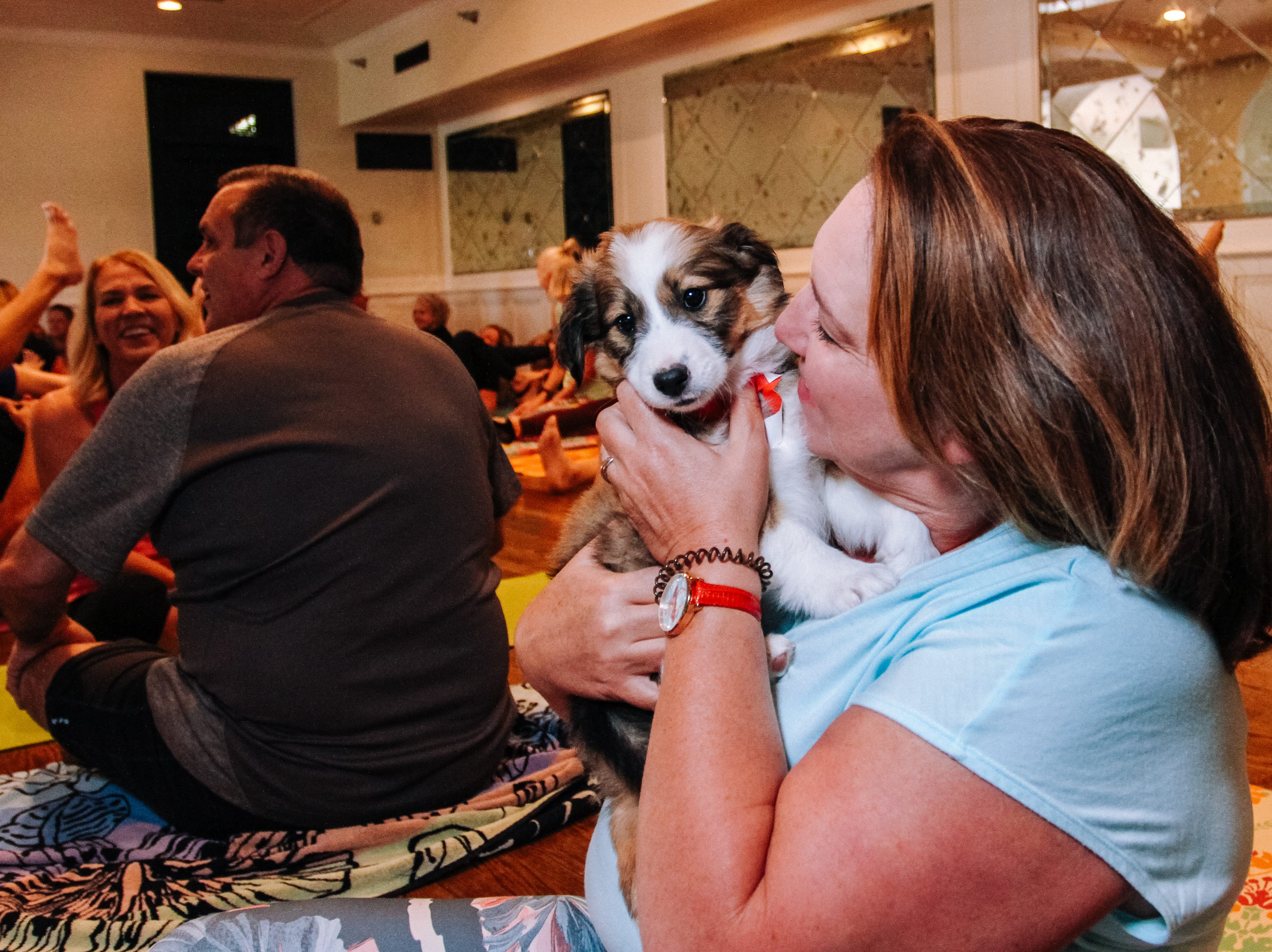 Amber Sangan plays with puppies at Puppies, Pilates and Prosecco, an event hosted by Almost There Foster Care at the Wrigley Mansion in Phoenix on April 13, 2019.