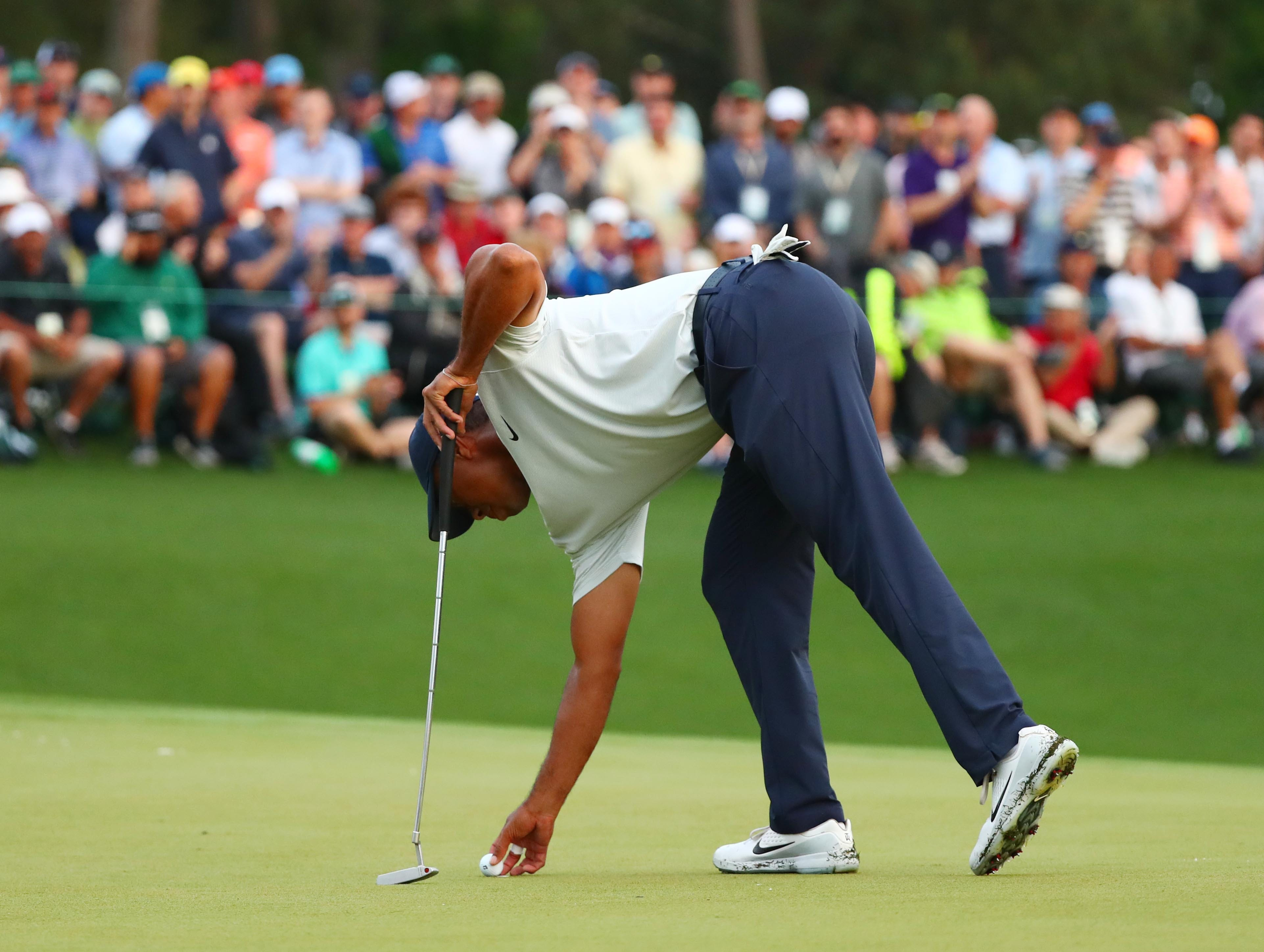 Apr 12, 2019; Augusta, GA, USA; Tiger Woods marks his ball spot on the 18th green during the second round of The Masters golf tournament at Augusta National Golf Club. Mandatory Credit: Rob Schumacher-USA TODAY Sports