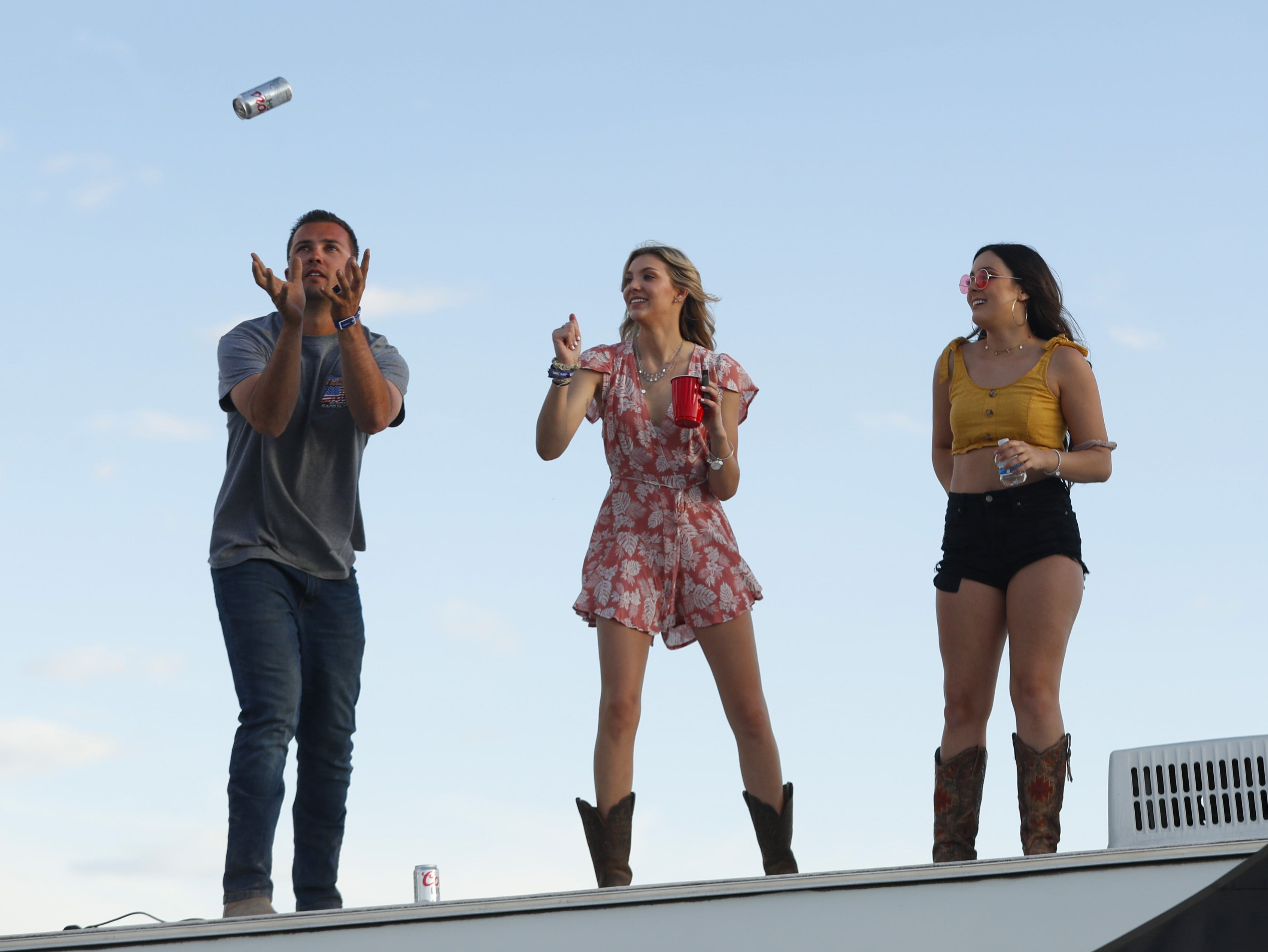 A beer is tossed to the top of a camper at the campsites during Country Thunder in Florence, Ariz. on Friday, April 12, 2019.