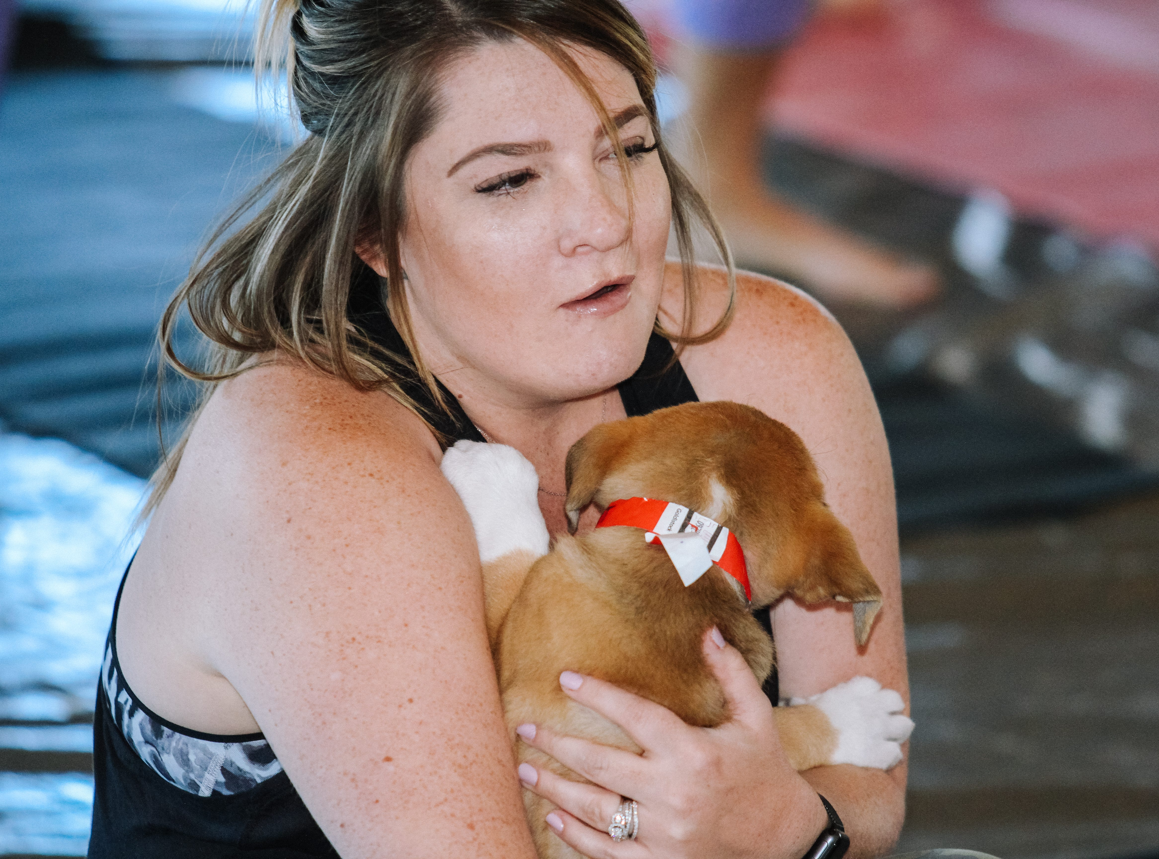 Caitlin Ristau plays with puppies at Puppies, Pilates and Prosecco, an event hosted by Almost There Foster Care at the Wrigley Mansion in Phoenix on April 13, 2019.