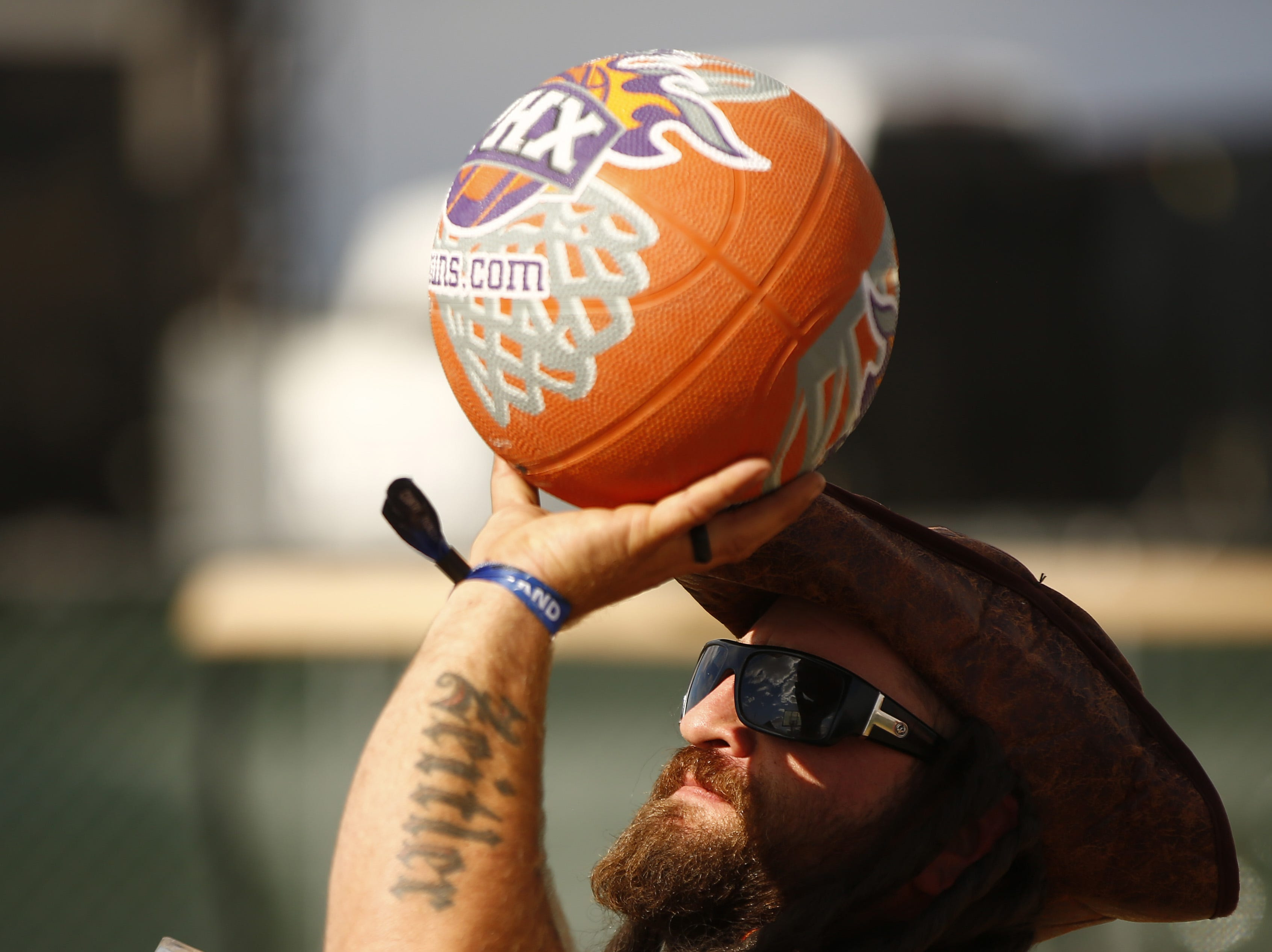 Pirate Chris Zeitler shoots baskets with Country musician Brandon Lay during a shootout for KMLE at Country Thunder in Florence, Ariz., on Friday, April 12, 2019.