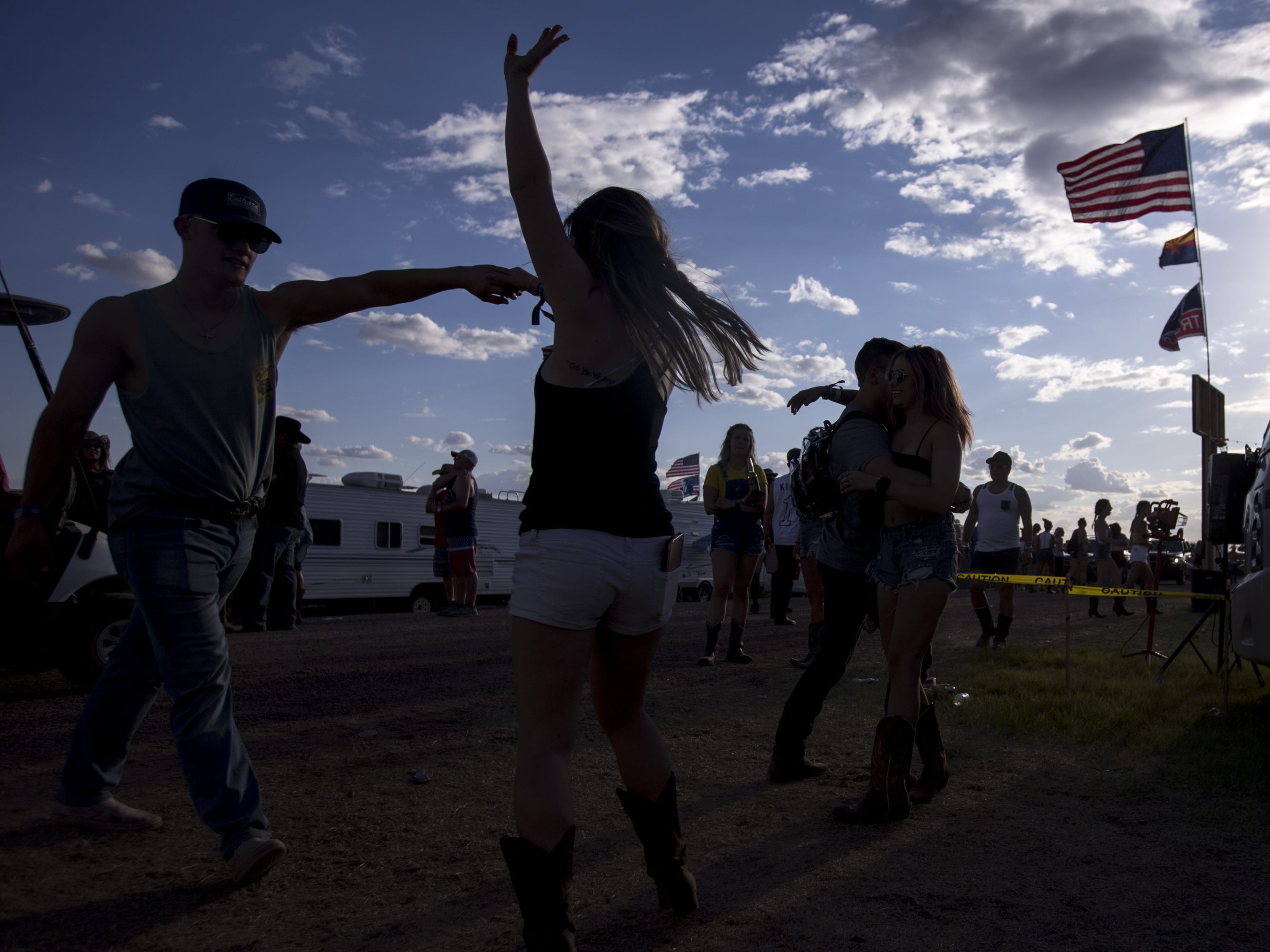 Festival-goers dance at the Crazy Coyote campground on Friday, April 12, 2019, during Day 2 of Country Thunder Arizona in Florence, Ariz.