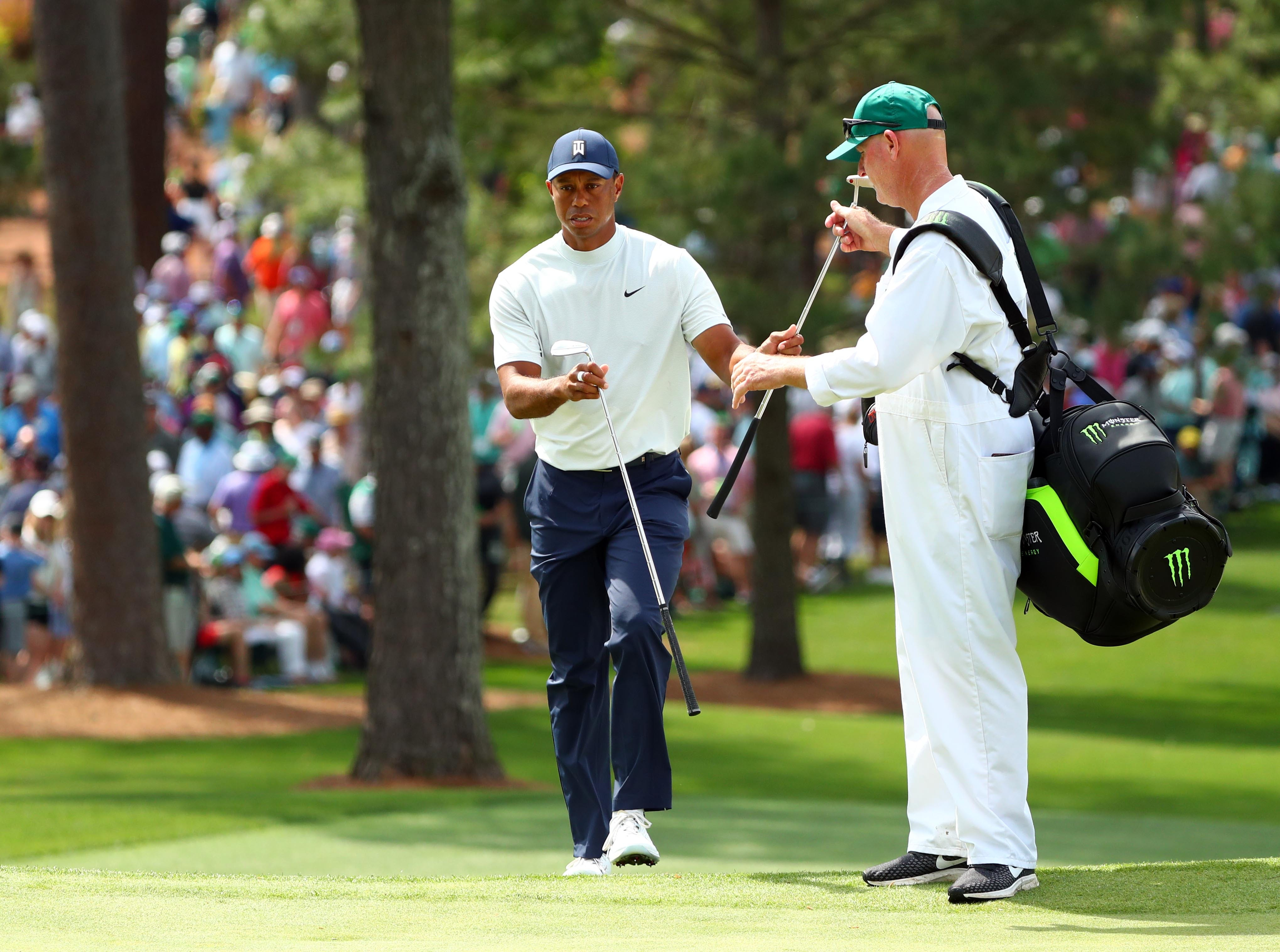 Apr 12, 2019; Augusta, GA, USA; Tiger Woods exchanges clubs with caddie Joe Lacava on the 7th green during the second round of The Masters golf tournament at Augusta National Golf Club. Mandatory Credit: Rob Schumacher-USA TODAY Sports