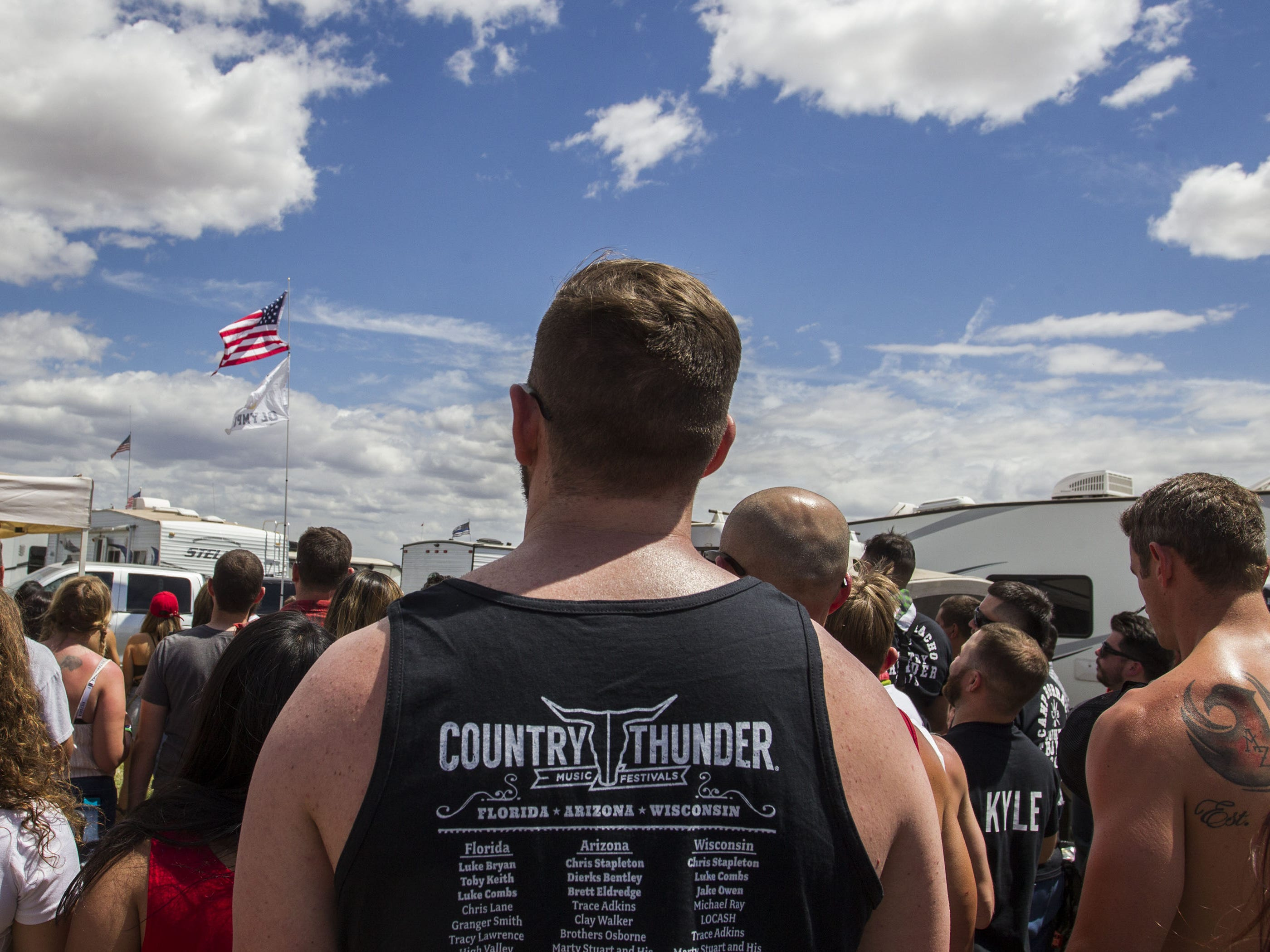 Beer Olympic participants stand for the National Anthem before their games at Country Thunder Arizona Friday, April 12, 2019, in Florence, Ariz.