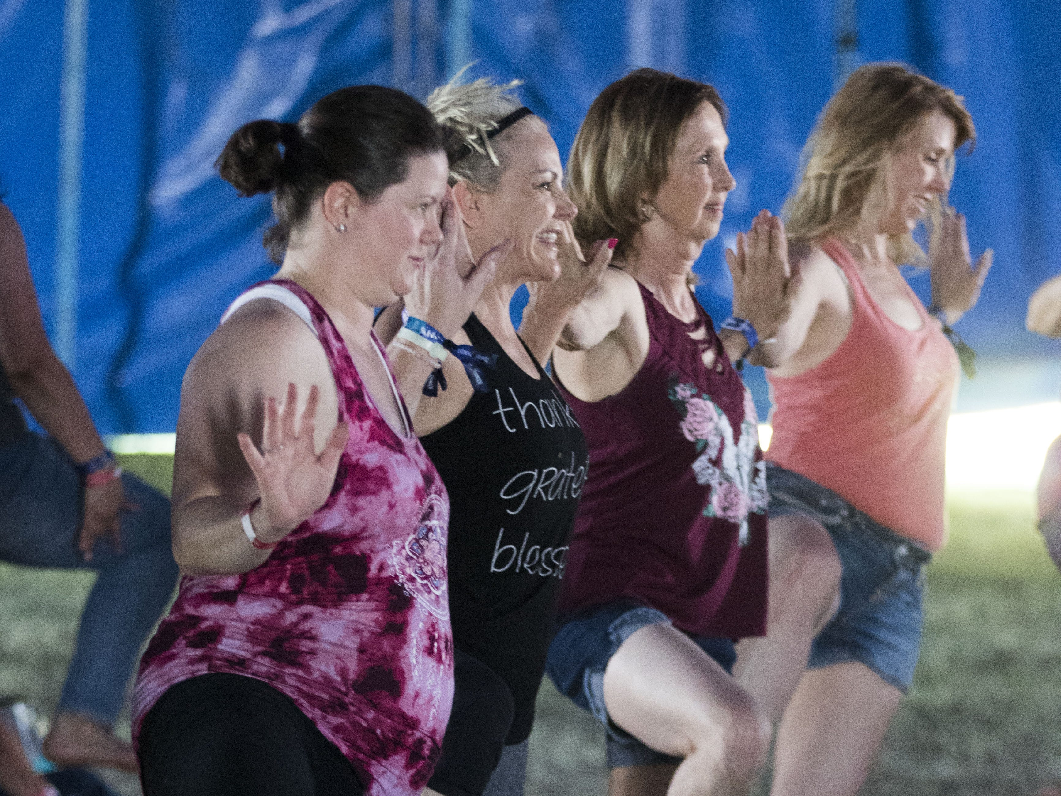 Women practice their balance during a yoga session at Country Thunder Arizona Saturday, April 13, 2019, in Florence, Ariz.