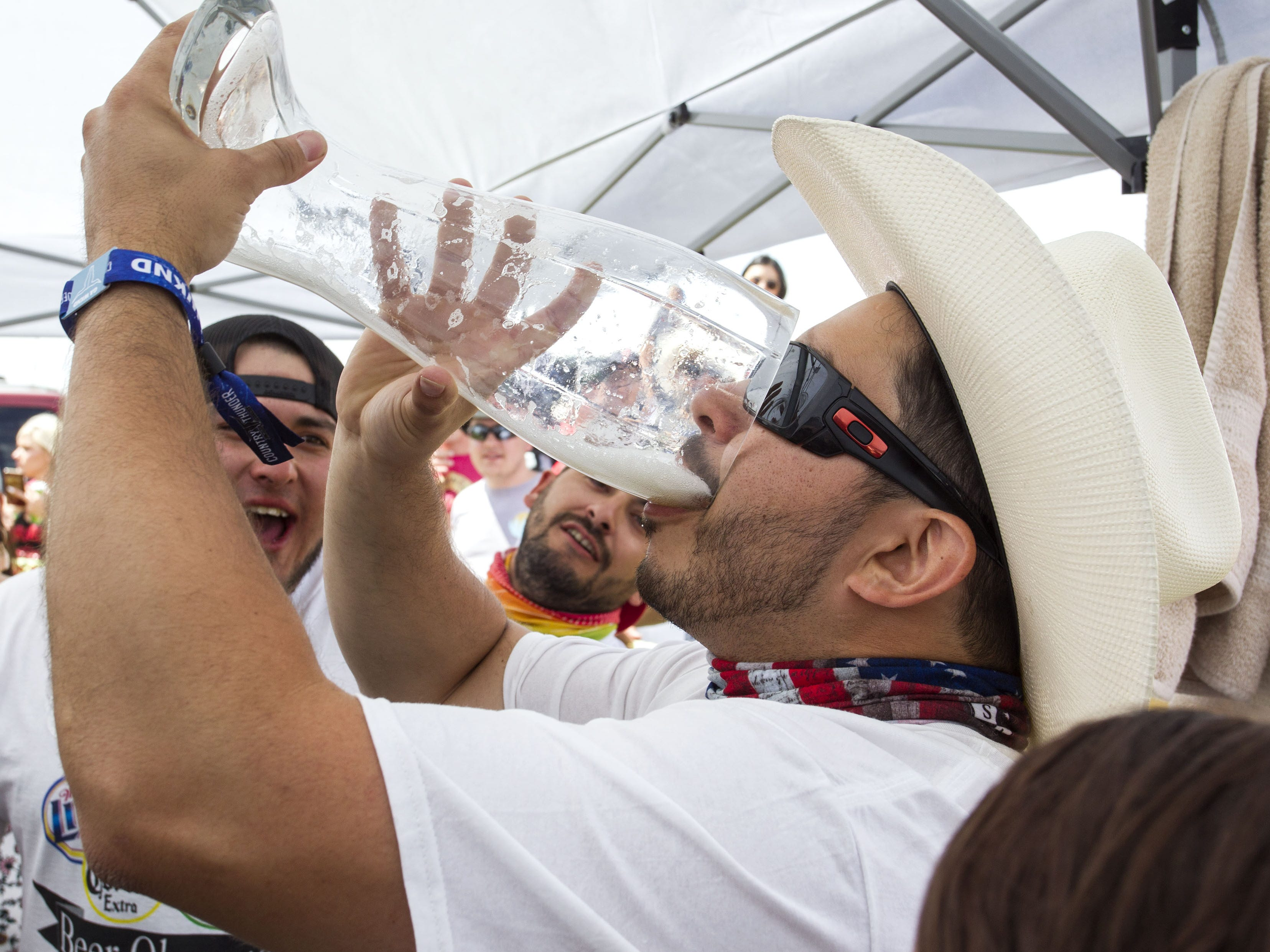 Last Chance Drunk Beer Olympian Justin Rodriguez downs the last sips of beer during the beer chugging game at Country Thunder Arizona Friday, April 12, 2019, in Florence, Ariz.