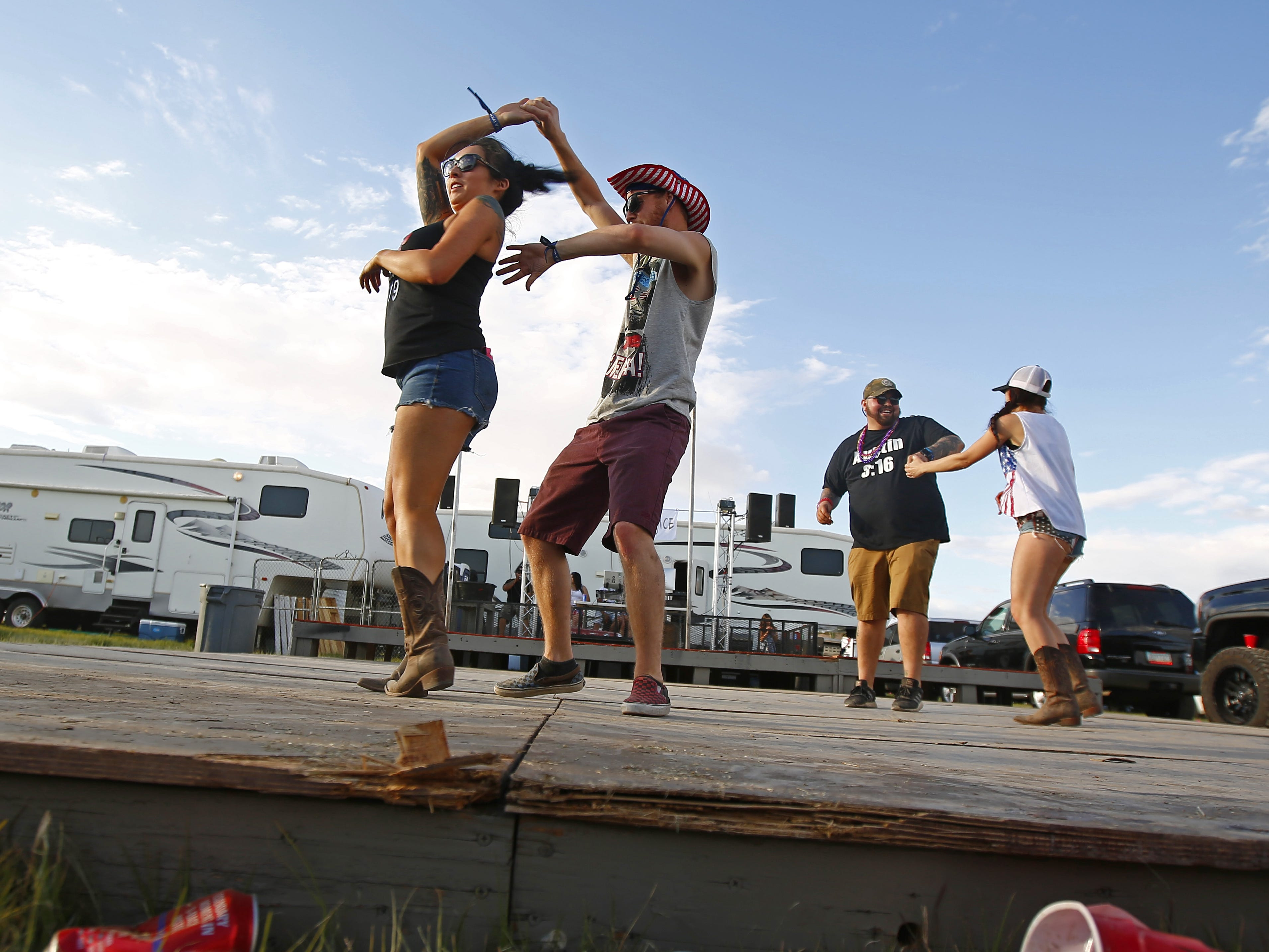 Casey Kaczmarowki spins Kristi Lovato as they dance on a stage at the campsite Coyote during Country Thunder in Florence, Ariz. on Friday, April 12, 2019.