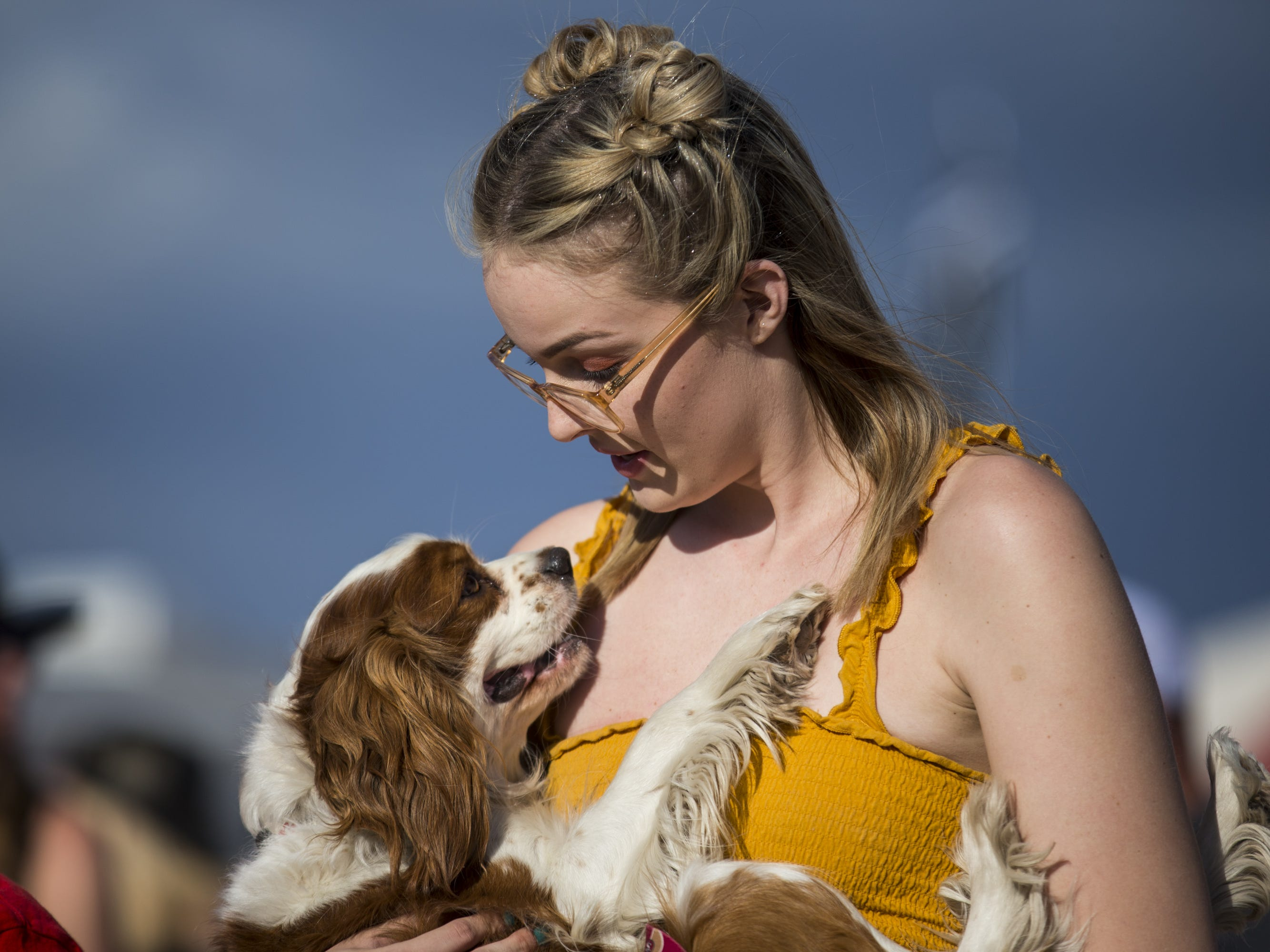 Gabby Raes carries her dog, Bentley, on Friday, April 12, 2019, during Day 2 of Country Thunder Arizona in Florence, Ariz.