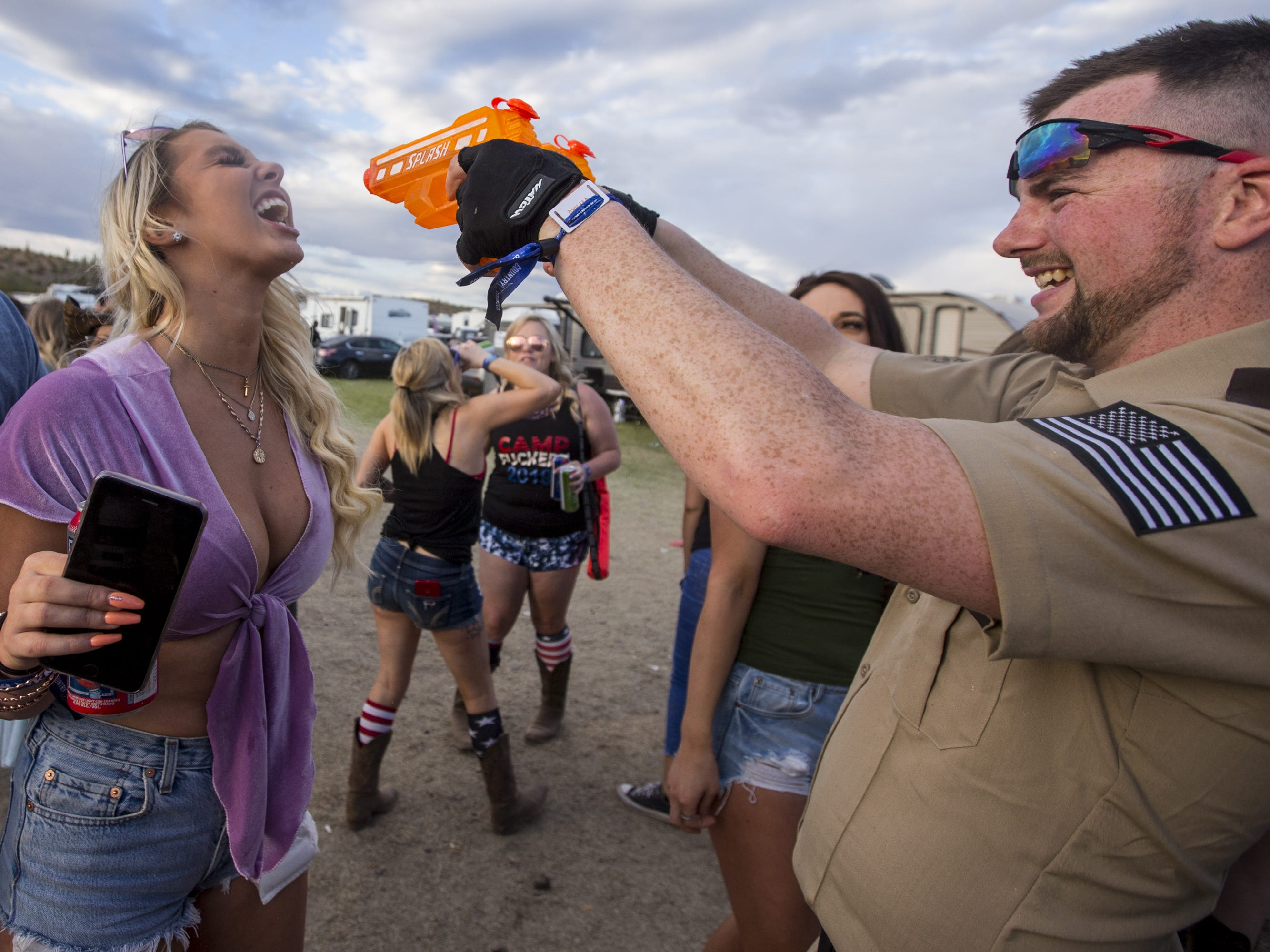 Luke Brown shoots liquor into Marlaina Hagen's mouth at the Crazy Coyote campground on Friday, April 12, 2019, during Day 2 of Country Thunder Arizona in Florence, Ariz.