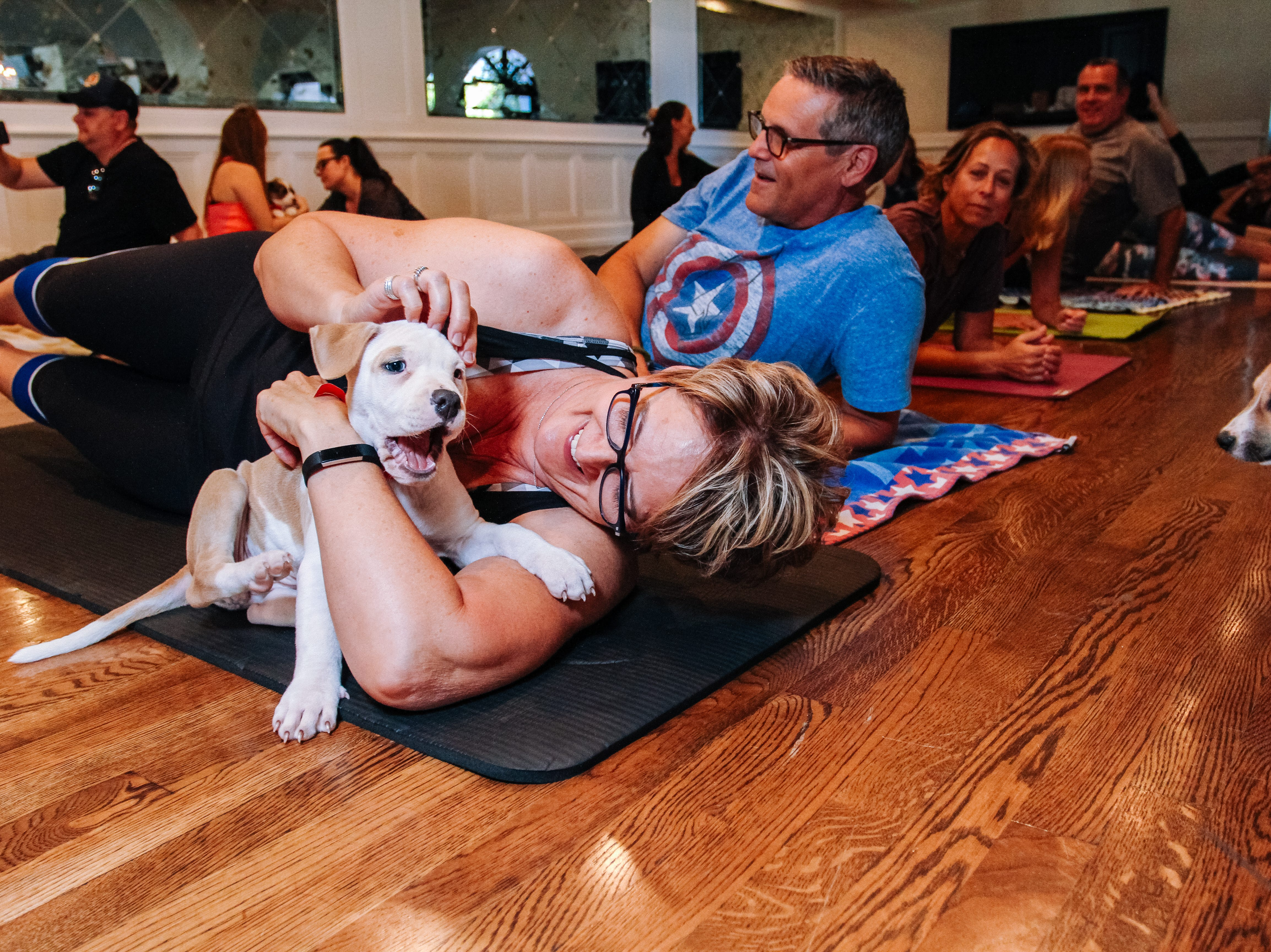 Lisa Akers plays with puppies at Puppies, Pilates and Prosecco, an event hosted by Almost There Foster Care at the Wrigley Mansion in Phoenix on April 13, 2019.