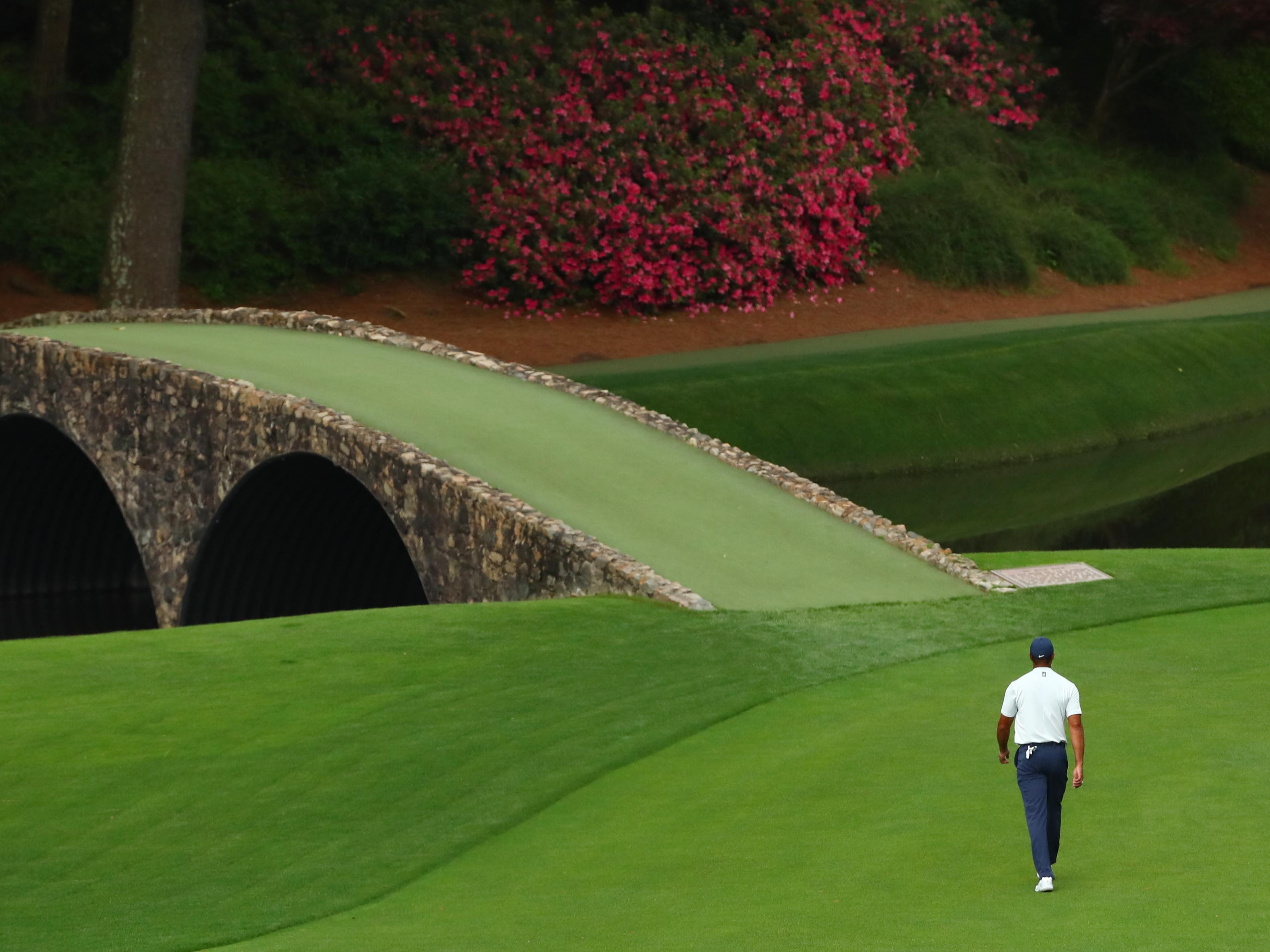 Apr 12, 2019; Augusta, GA, USA; Tiger Woods walks across the Hogan Bridge to mark his ball on the 12th green after play is suspended during the second round of The Masters golf tournament at Augusta National Golf Club. Mandatory Credit: Rob Schumacher-USA TODAY Sports