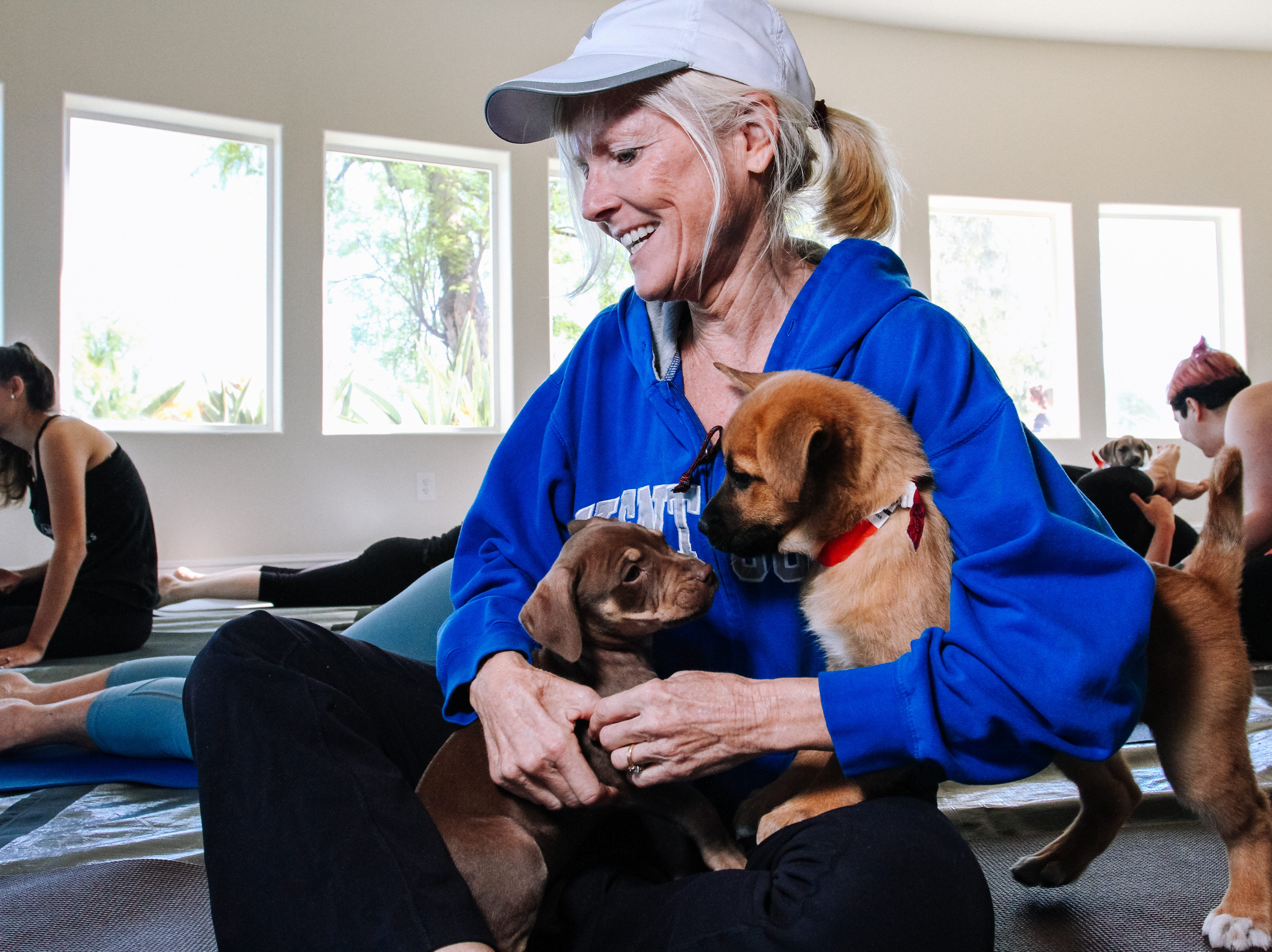 Mary Beth Thomas plays with puppies at Puppies, Pilates and Prosecco, an event hosted by Almost There Foster Care at the Wrigley Mansion in Phoenix on April 13, 2019.