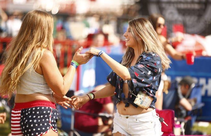 Ashley Tutherow (left) dances with Belen Bustillos as they listen to Abby Anderson during Country Thunder in Florence, Ariz., on Friday, April 12, 2019.