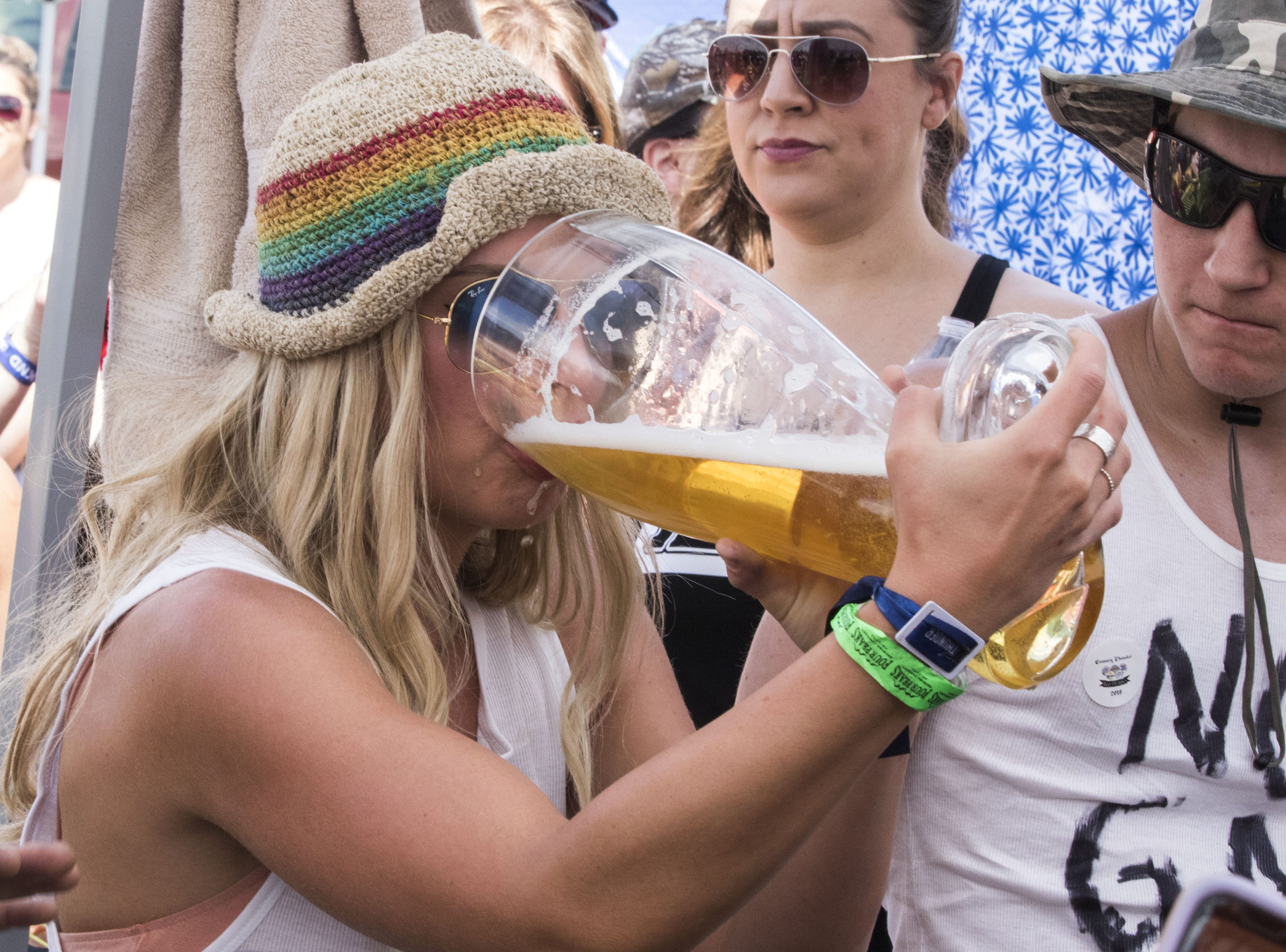 A Beer Olympian does her best at chugging her beer during the beer chugging game at Country Thunder Arizona Friday, April 12, 2019, in Florence, Arizona.
