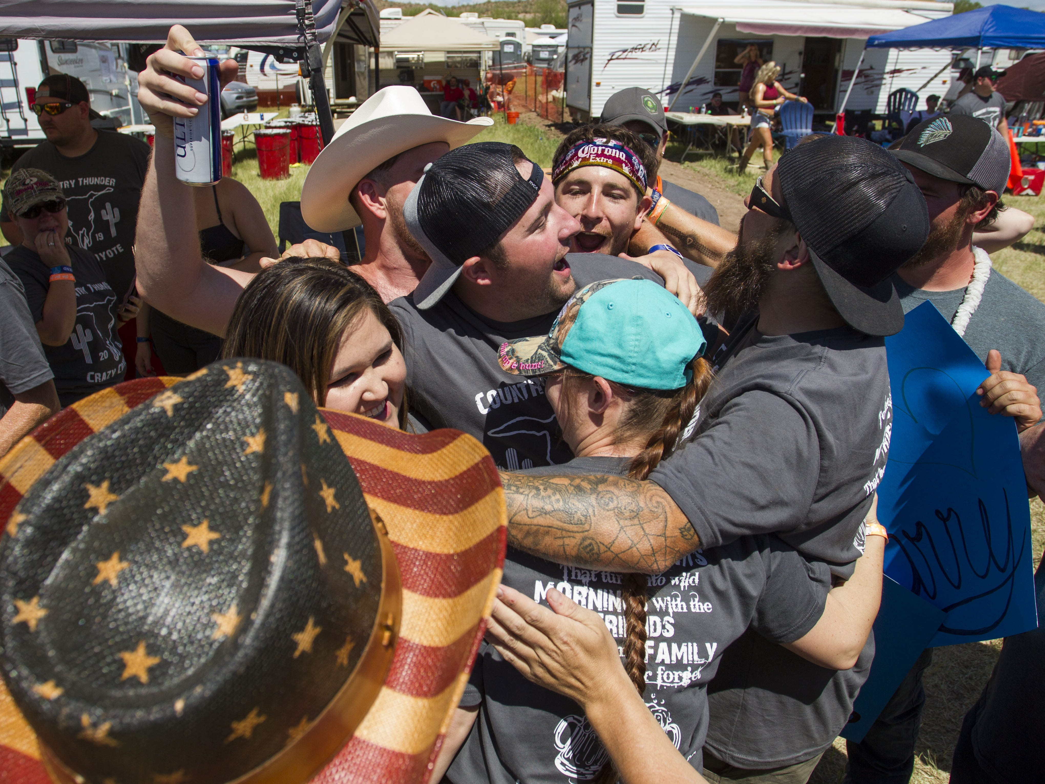 """Family and friends mob Tahnee Billingsly after she said """"yes"""" during a marriage proposal at Country Thunder Arizona Saturday, April 13, 2019, in Florence, Ariz."""
