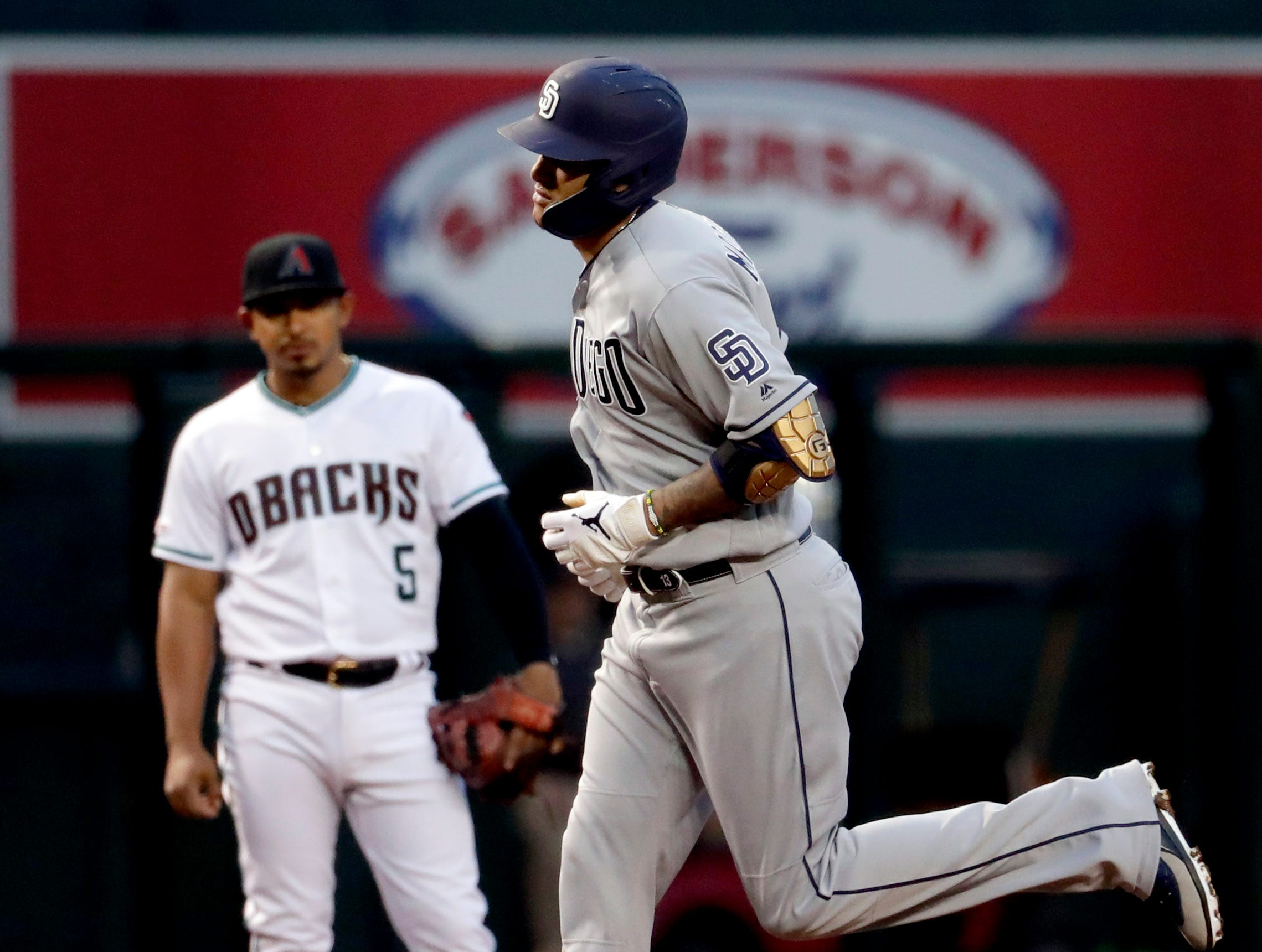 San Diego Padres' Manny Machado rounds the bases after hitting a solo home run as Arizona Diamondbacks Eduardo Escobar (5) looks on during the first inning of a baseball game, Friday, April 12, 2019, in Phoenix. (AP Photo/Matt York)