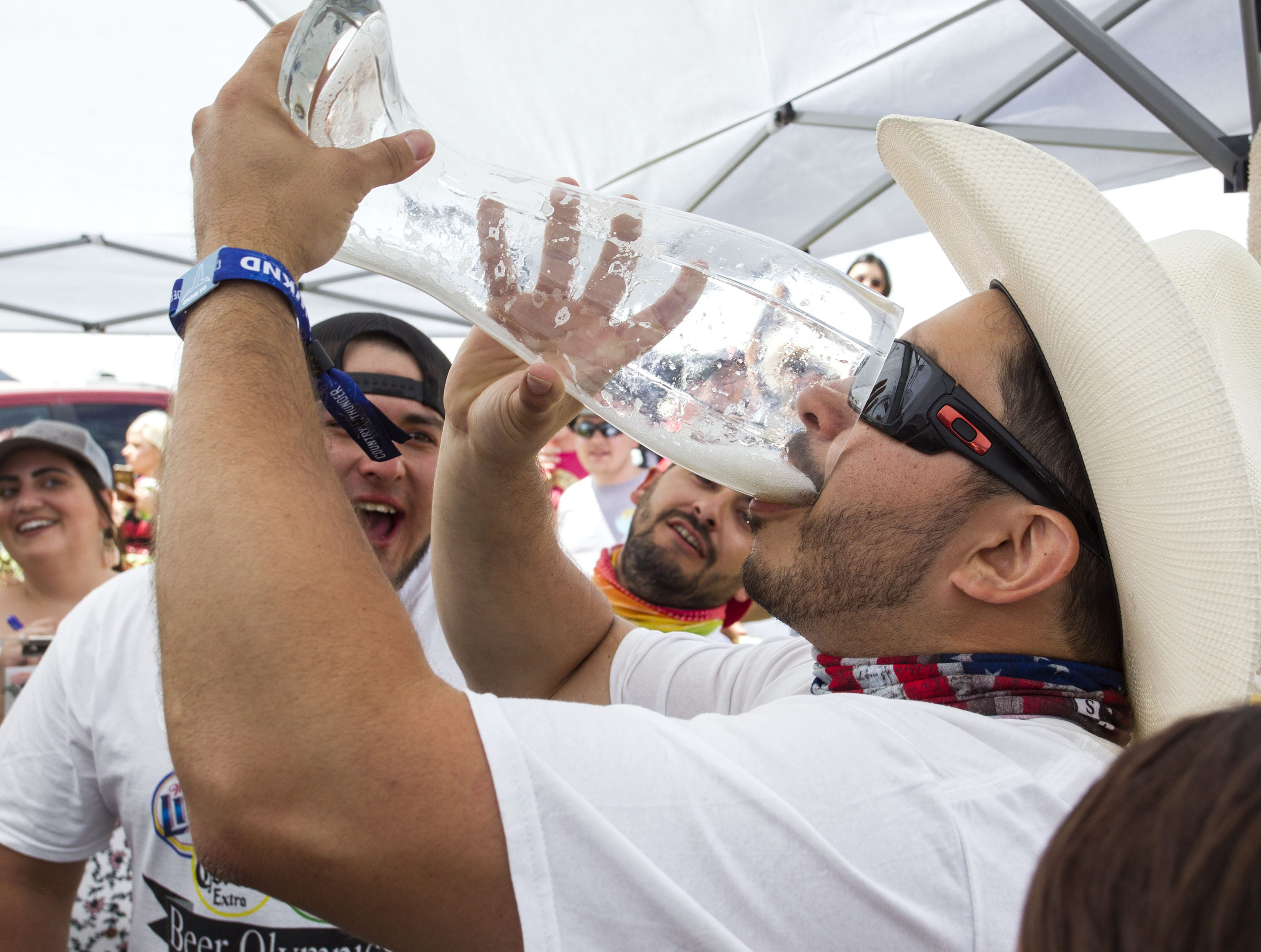 With his teammates cheering him on, Last Chance Drunk Beer Olympian Justin Rodriguez downs the last sips of beer during the beer chugging game at Country Thunder Arizona Friday, April 12, 2019, in Florence, Arizona.