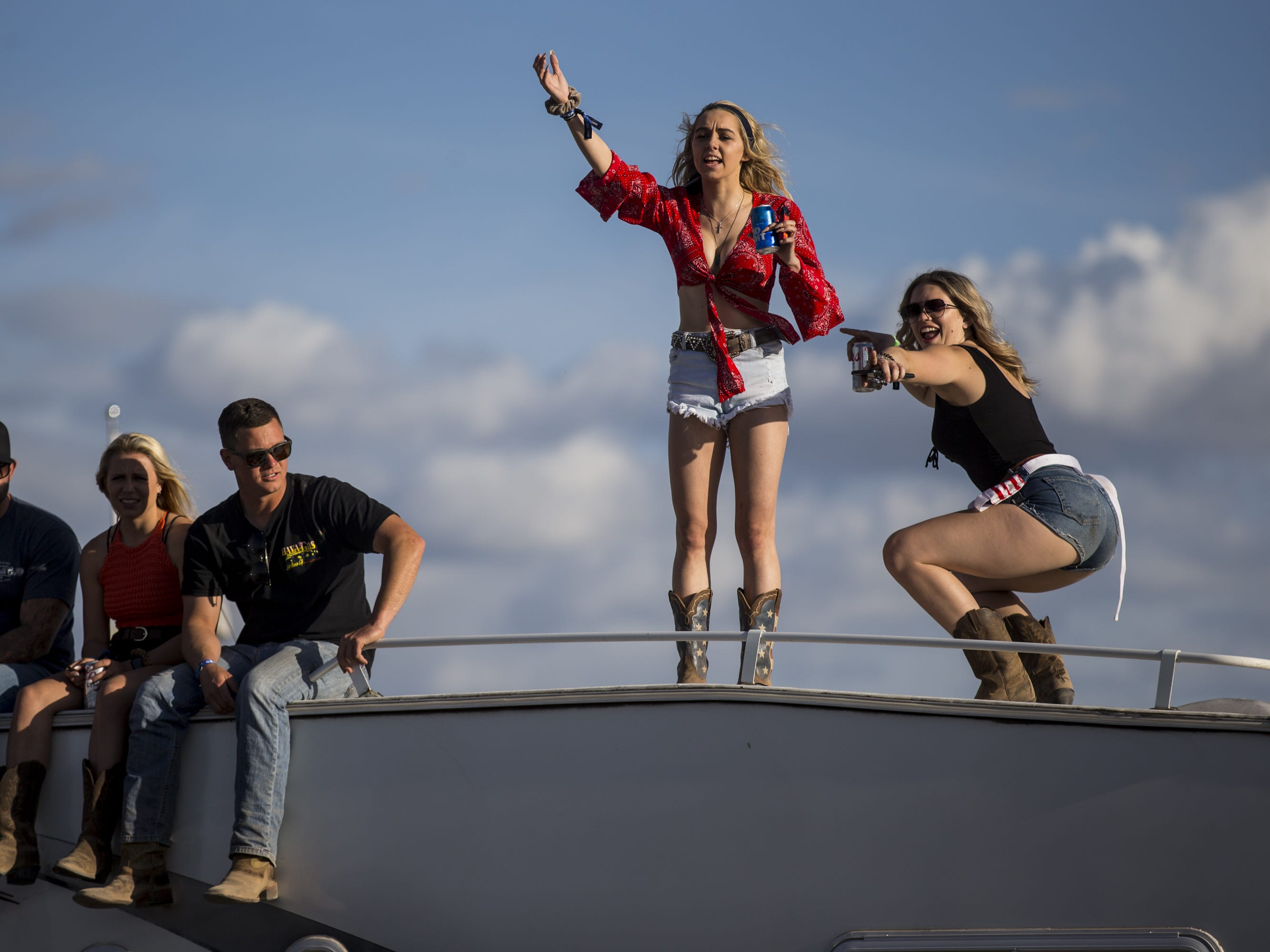 Festival-goers dance on top of an RV on Friday, April 12, 2019, during Day 2 of Country Thunder Arizona in Florence, Ariz.