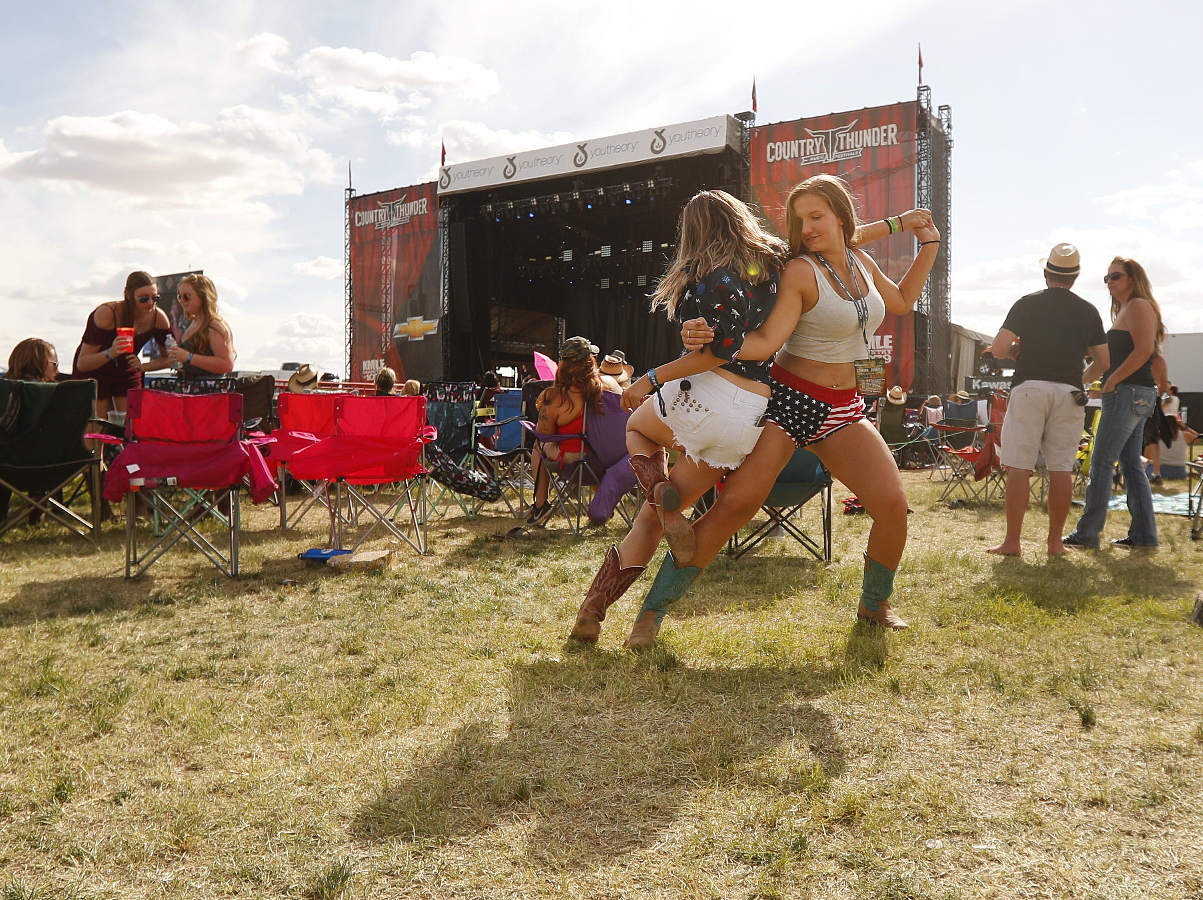 Ashley Tutherow (right) dances with Belen Bustillos as they listen to Abby Anderson during Country Thunder in Florence, Ariz., on Friday, April 12, 2019.