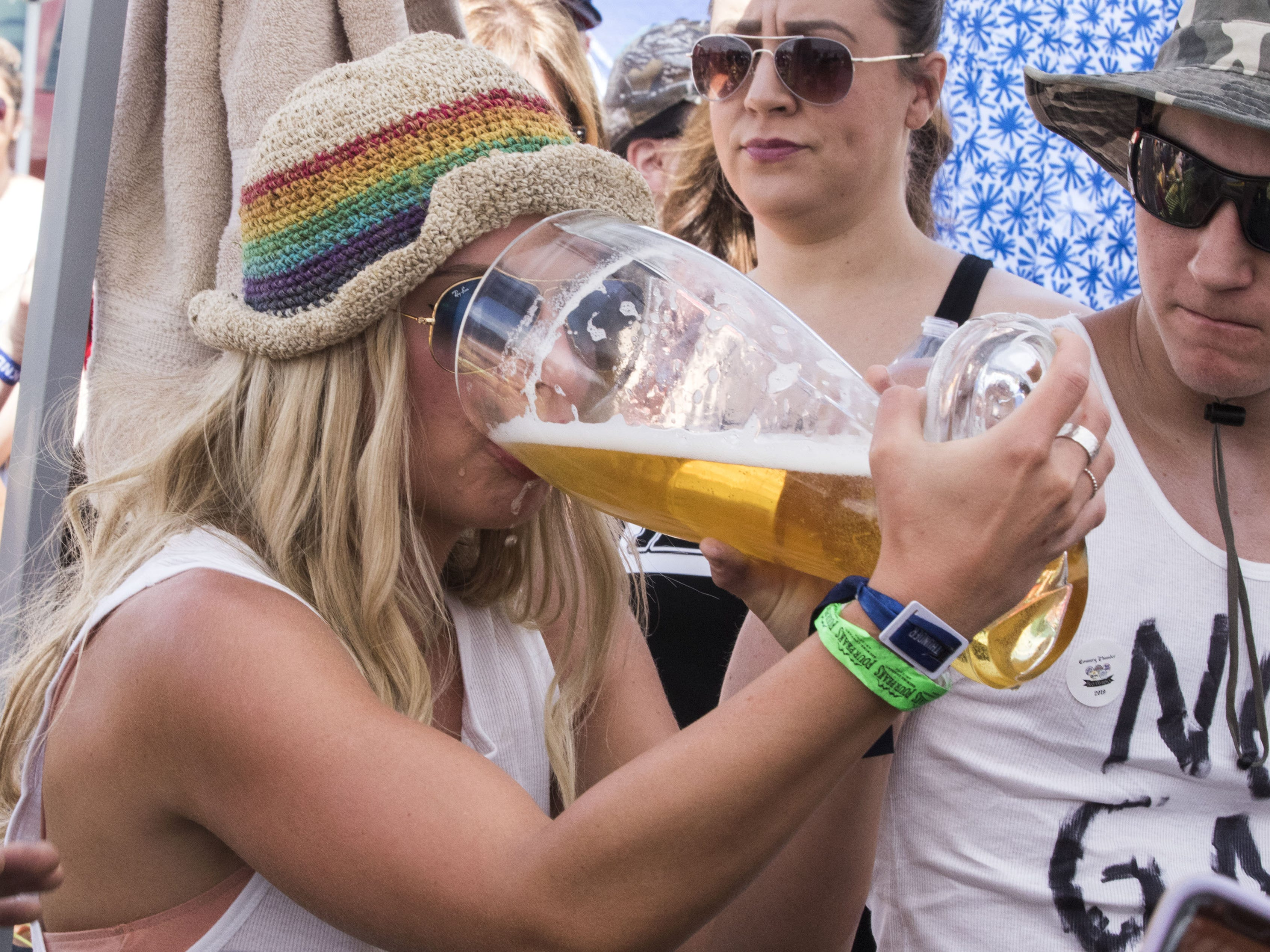 A Beer Olympian chugs her beer during the beer chugging game at Country Thunder Arizona Friday, April 12, 2019, in Florence, Ariz.