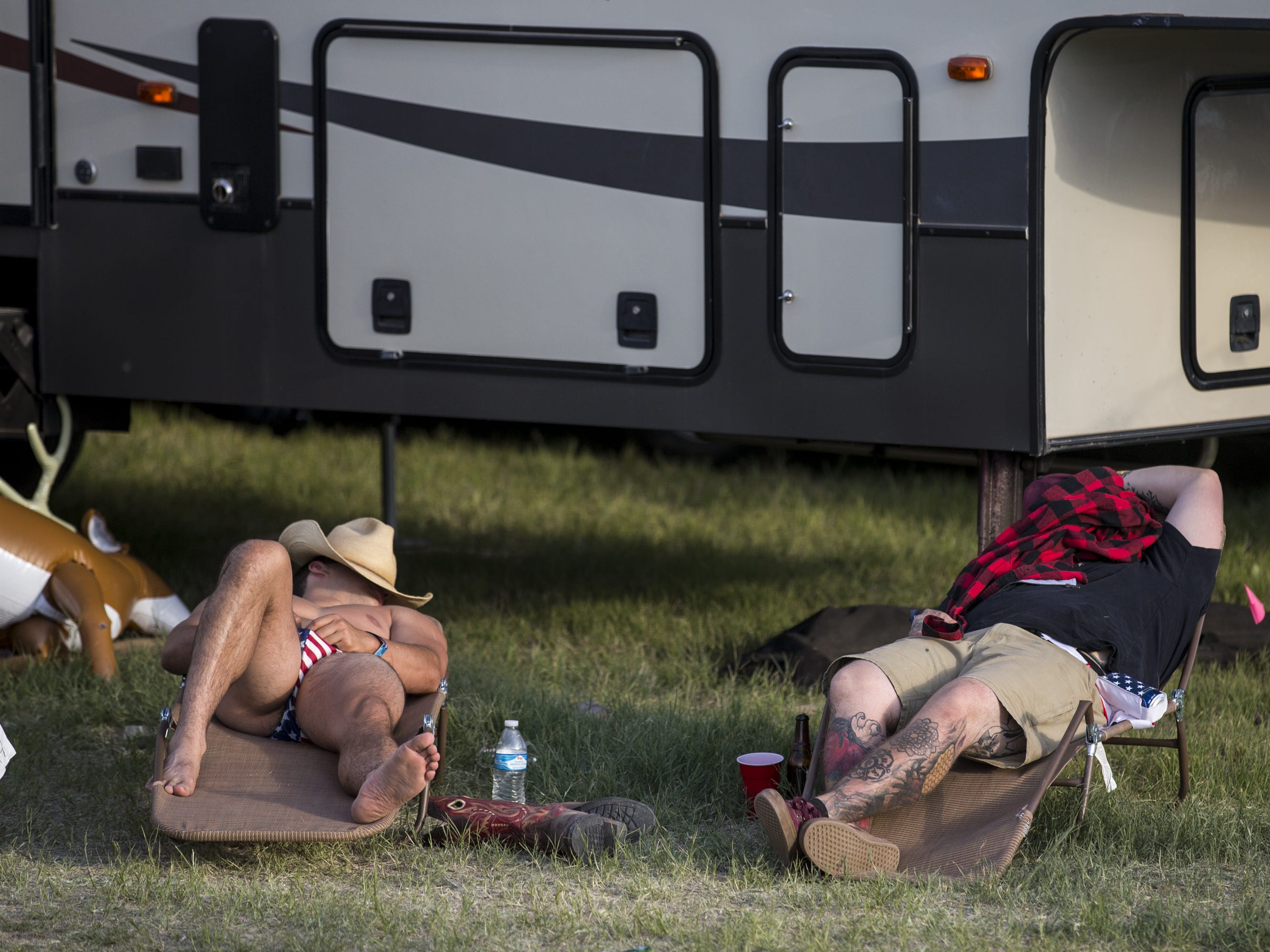 Festival-goers sleep outside an RV on Friday, April 12, 2019, during Day 2 of Country Thunder Arizona in Florence, Ariz.