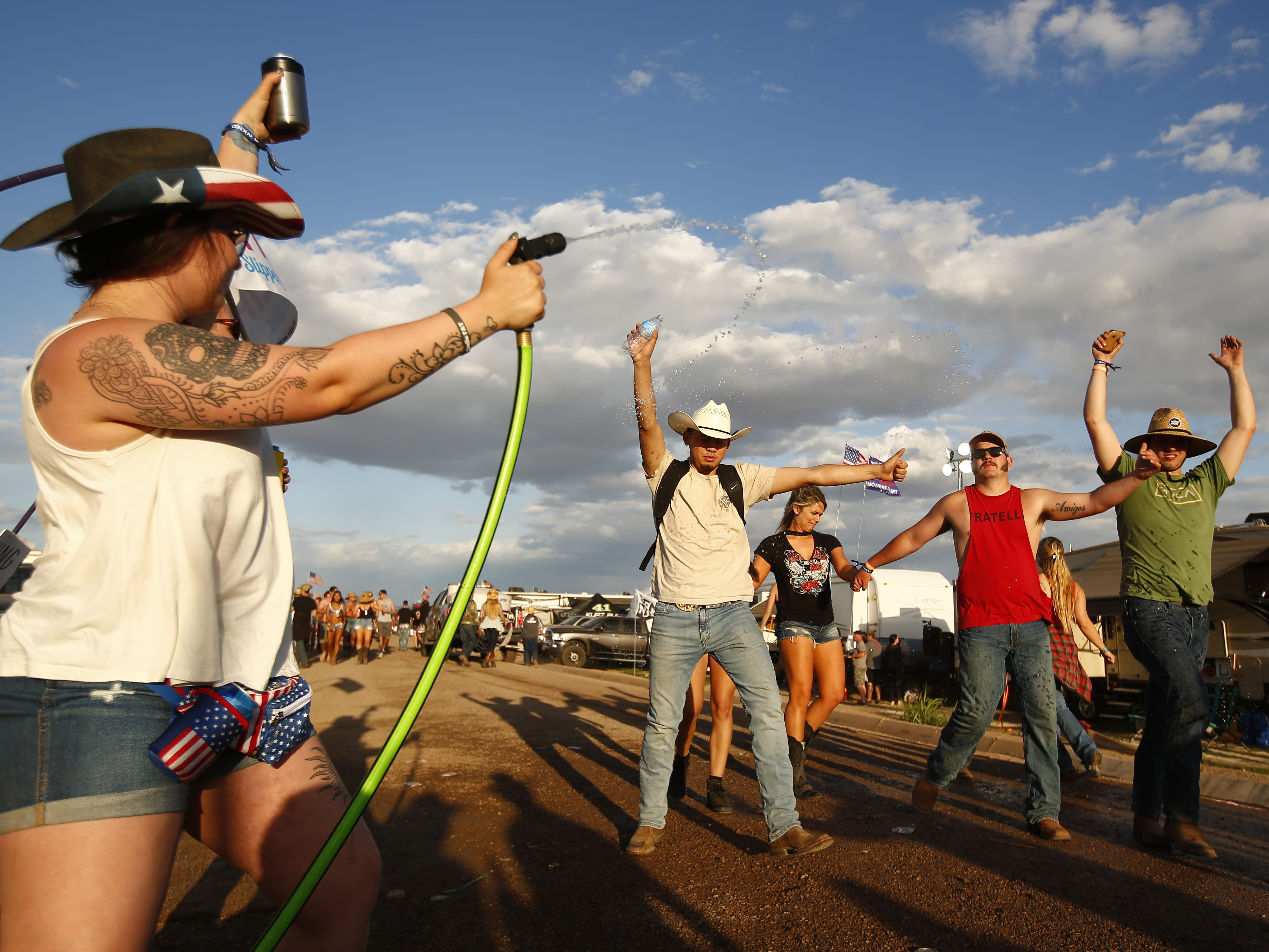 Country music fans are sprayed with water at the campsites during Country Thunder in Florence, Ariz. on Friday, April 12, 2019.