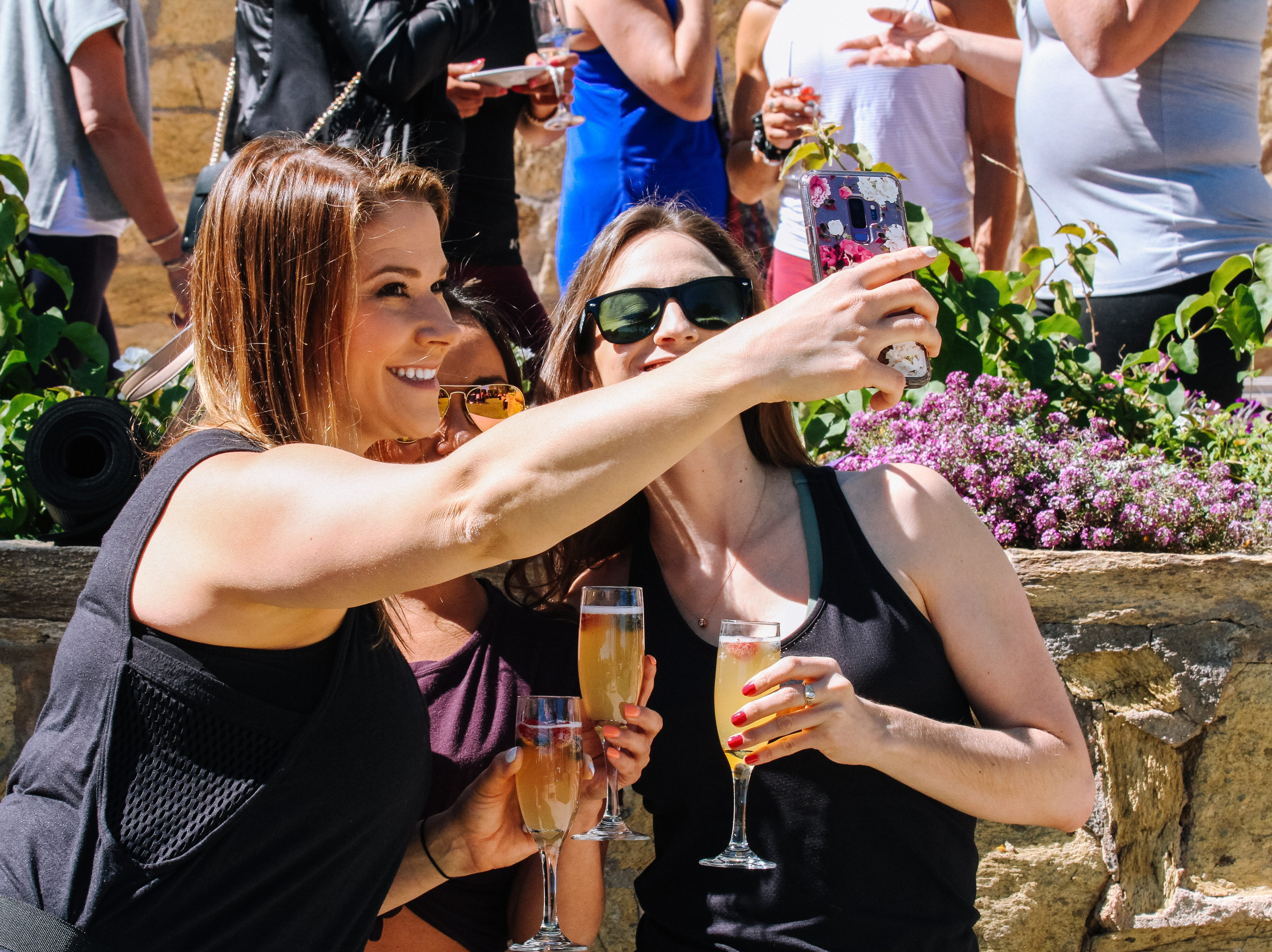 Attendees get food and drink after playing with puppies at Puppies, Pilates and Prosecco, an event hosted by Almost There Foster Care at the Wrigley Mansion in Phoenix on April 13, 2019.