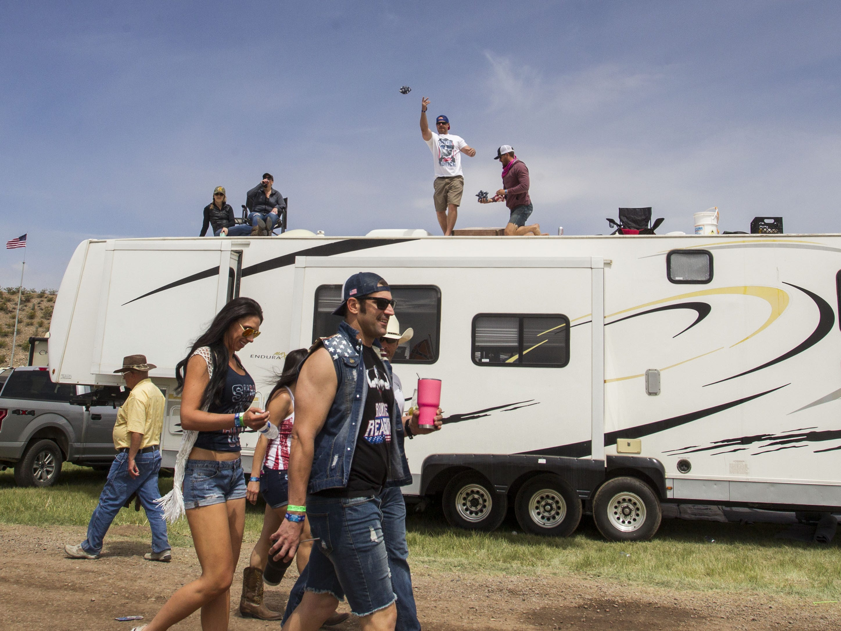 Party-goers play long toss cornhole off the top of their RV during Country Thunder Arizona Friday, April 12, 2019, in Florence, Ariz.