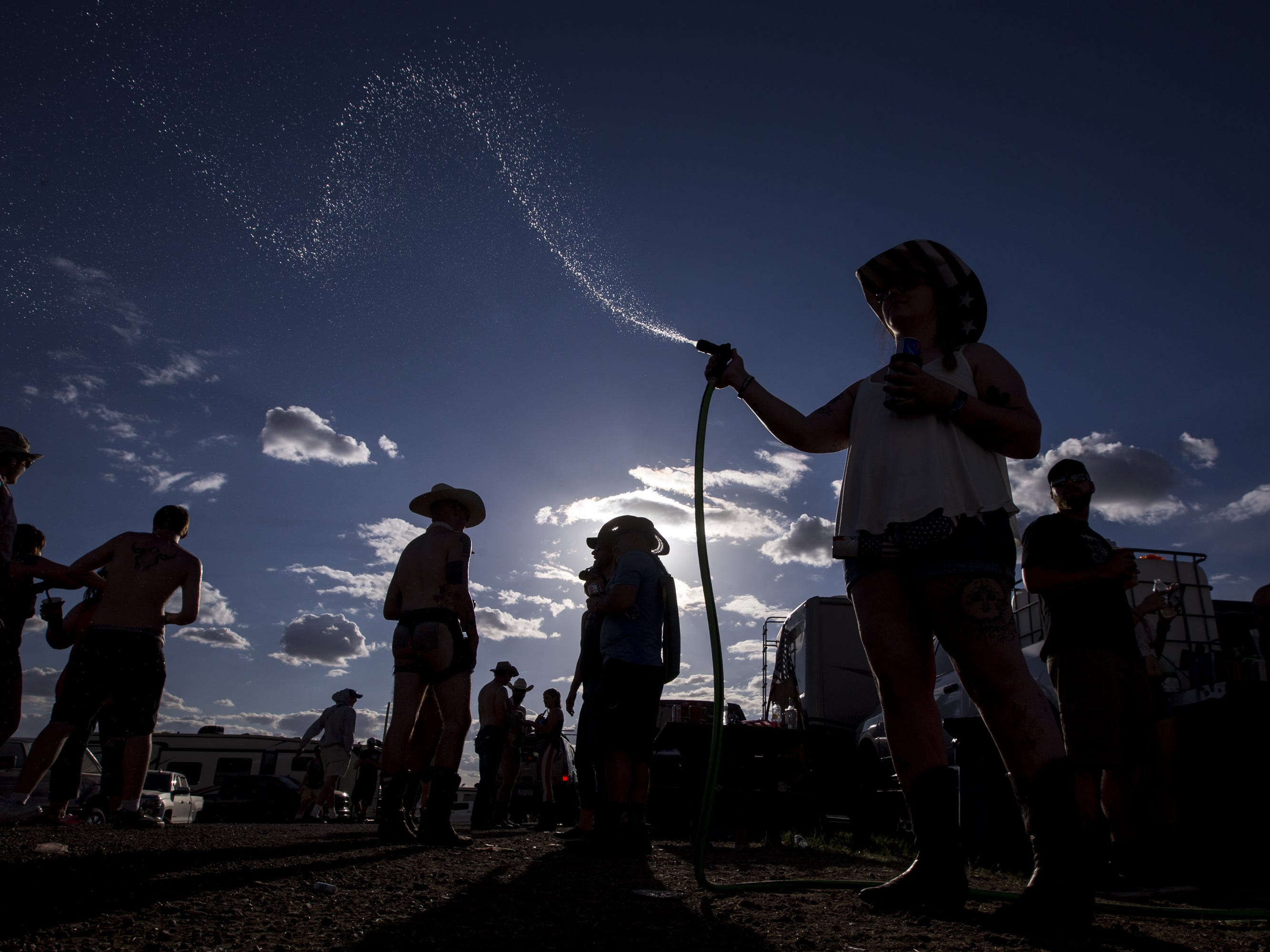Kamiah Ruesga sprays people with water at the Crazy Coyote campground on Friday, April 12, 2019, during Day 2 of Country Thunder Arizona in Florence, Ariz.