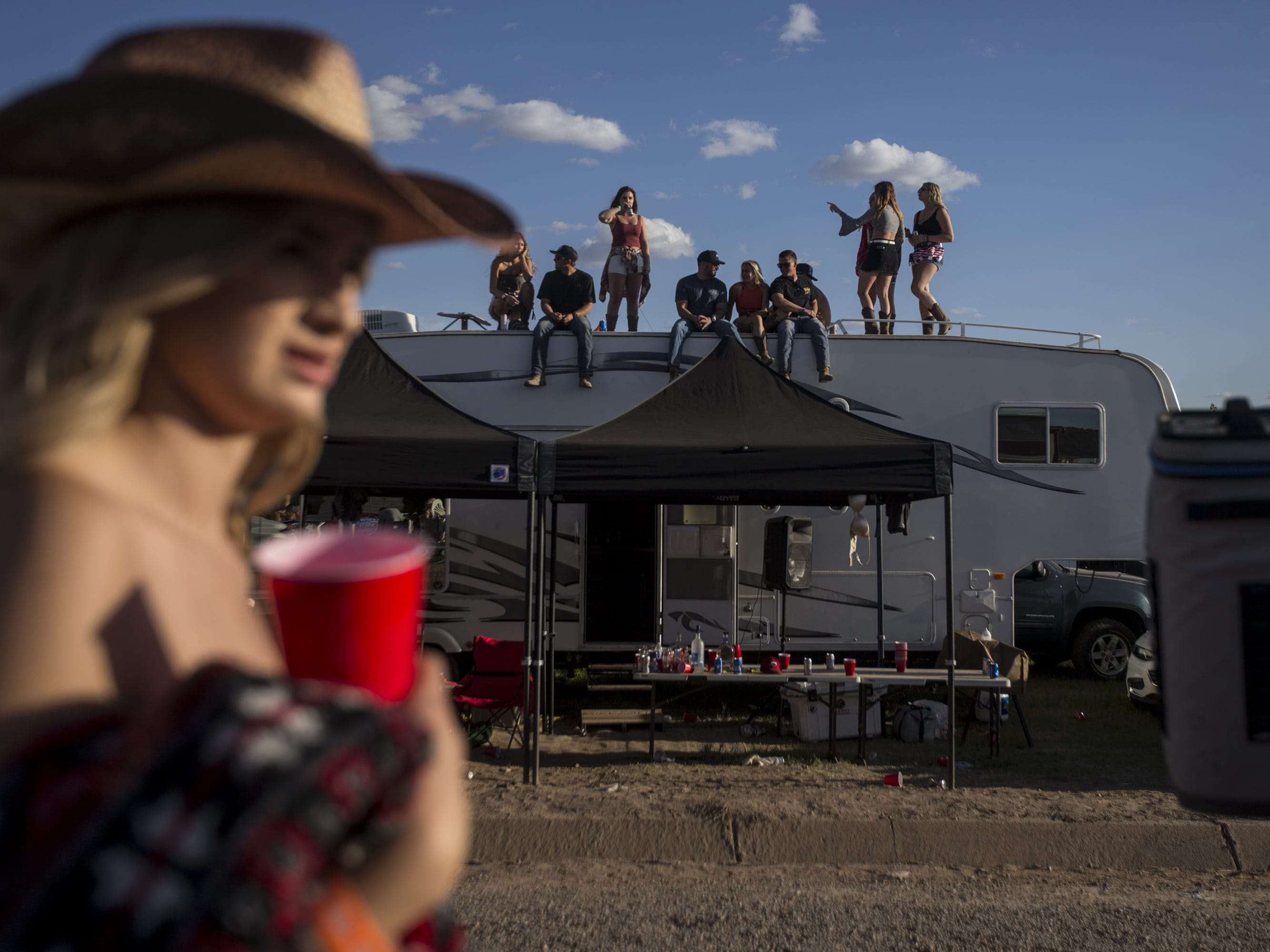 Festival-goers stand on top of an RV on Friday, April 12, 2019, during Day 2 of Country Thunder Arizona in Florence, Ariz.