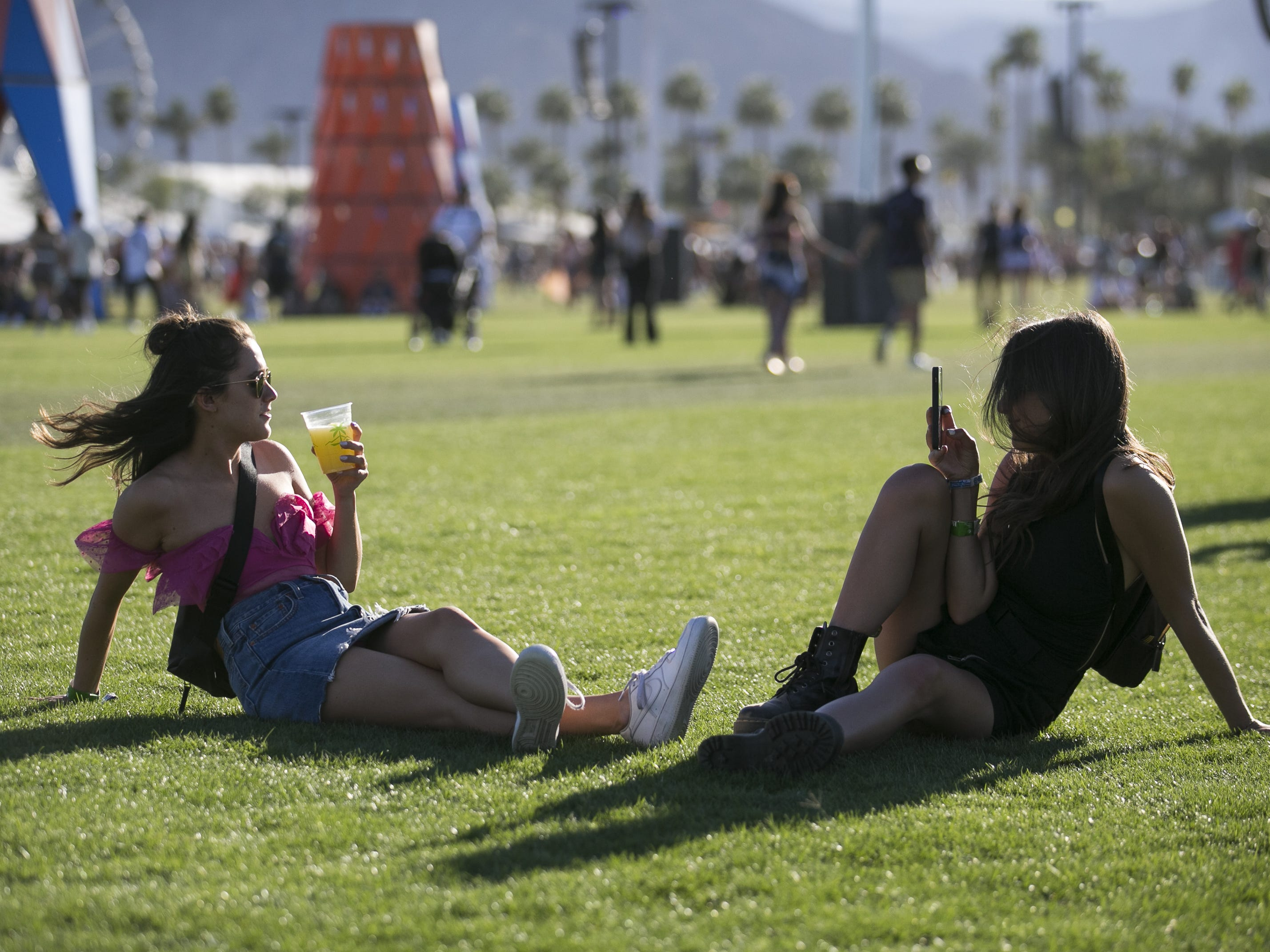 Savanna Stephens (left) and Ally Lucchesi (right) both from Los Angeles, sit in the grass at the Coachella Valley Music and Arts Festival in Indio, Calif. on April 12, 2019.