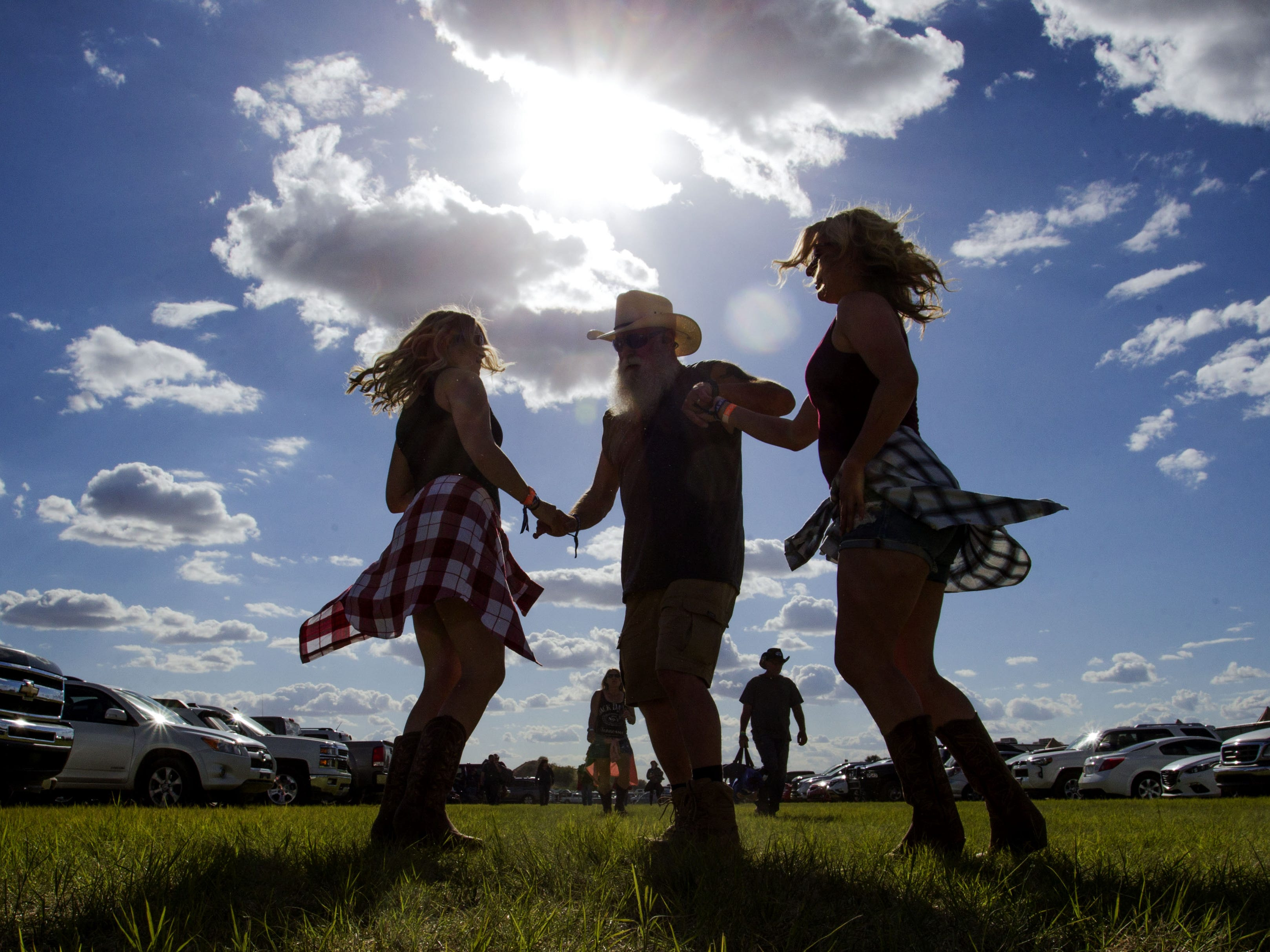 Jerry McElhaney dances with his daughter Piper and Kelley Seale in the parking lot of Country Thunder Arizona Friday, April 12, 2019, in Florence, Ariz.