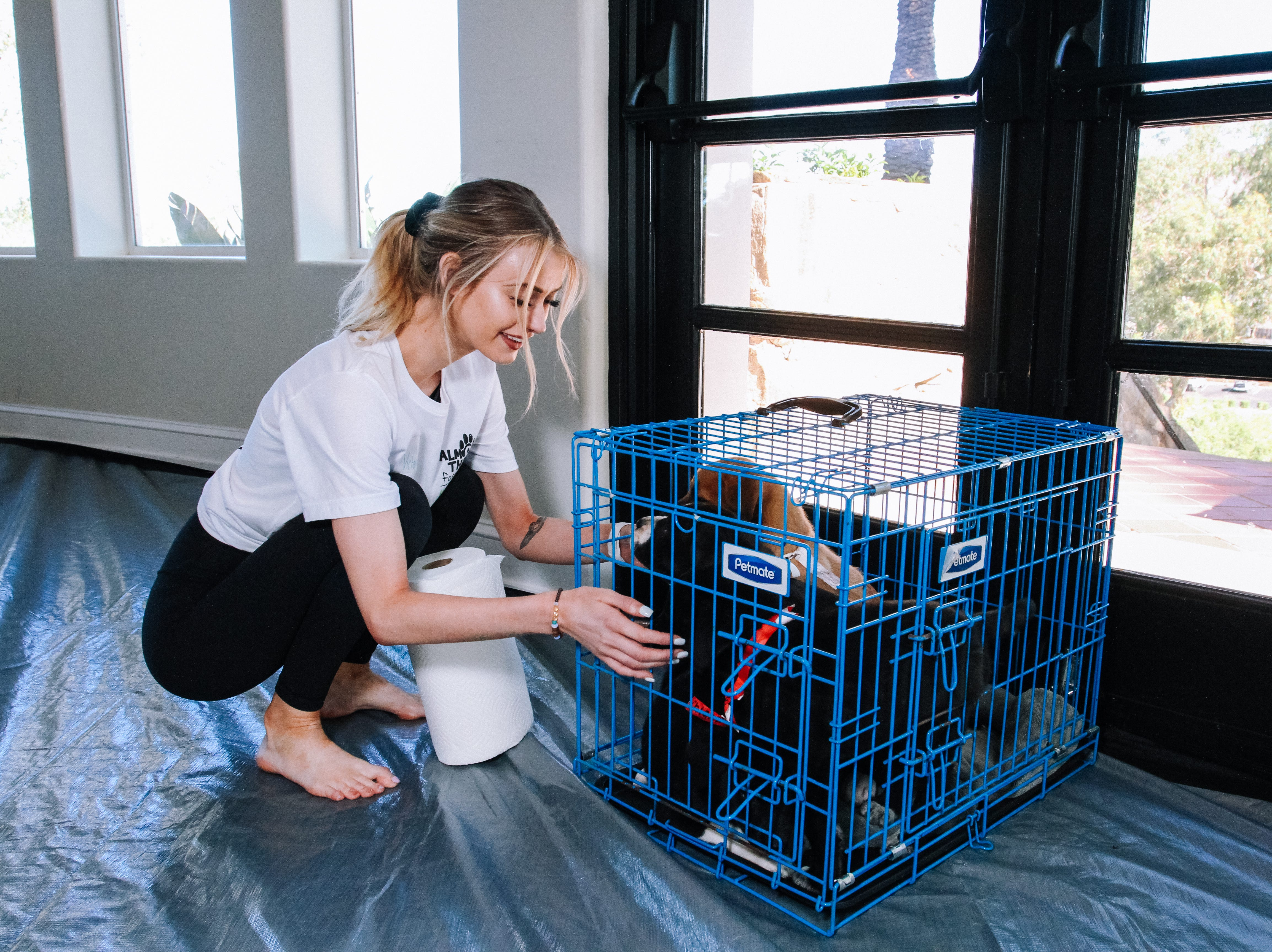 Victoria Eccles, a volunteer with Almost There Foster Care, puts puppies in their kennel at Puppies, Pilates and Prosecco, an event hosted by Almost There Foster Care at the Wrigley Mansion in Phoenix on April 13, 2019.