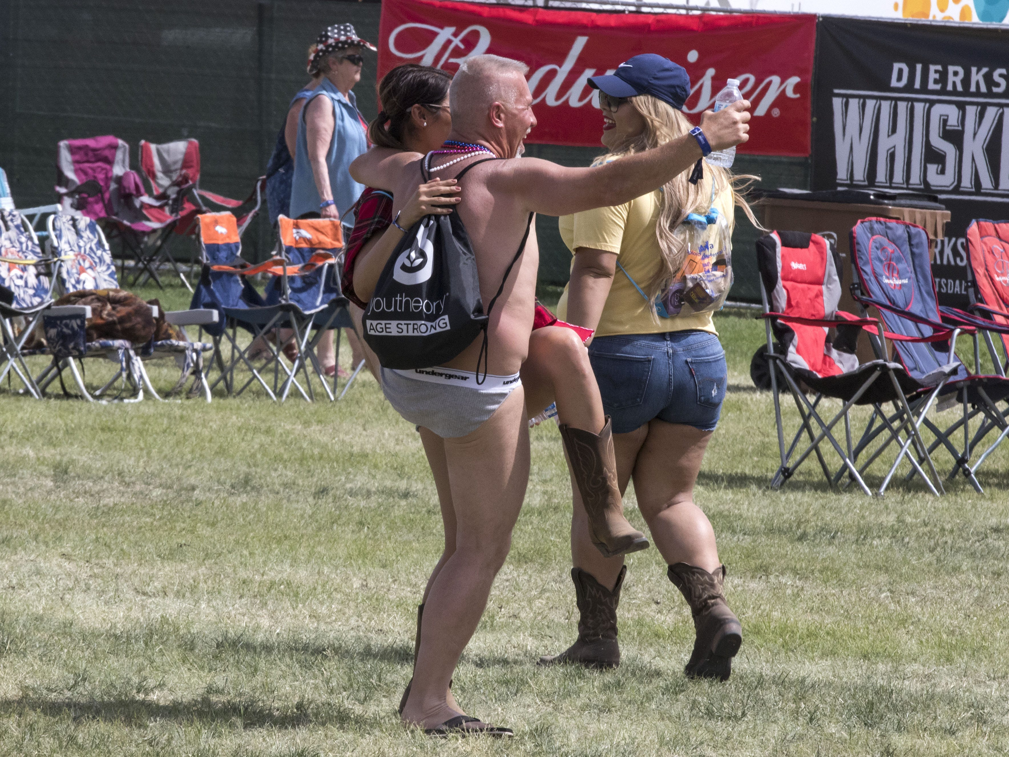 Donning only bikini briefs, flip flops and a backpack, John Schmidt of Mesa laughs during Country Thunder Arizona Friday, April 12, 2019, in Florence, Ariz.