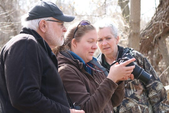 Tim Daniel, left, a photographer with the ODNR Division of Wildlife, and professional nature photographer Nina Harfmann, right, offer tips to Christina Kuchle, who traveled from Hancock County for a workshop at Magee Marsh.