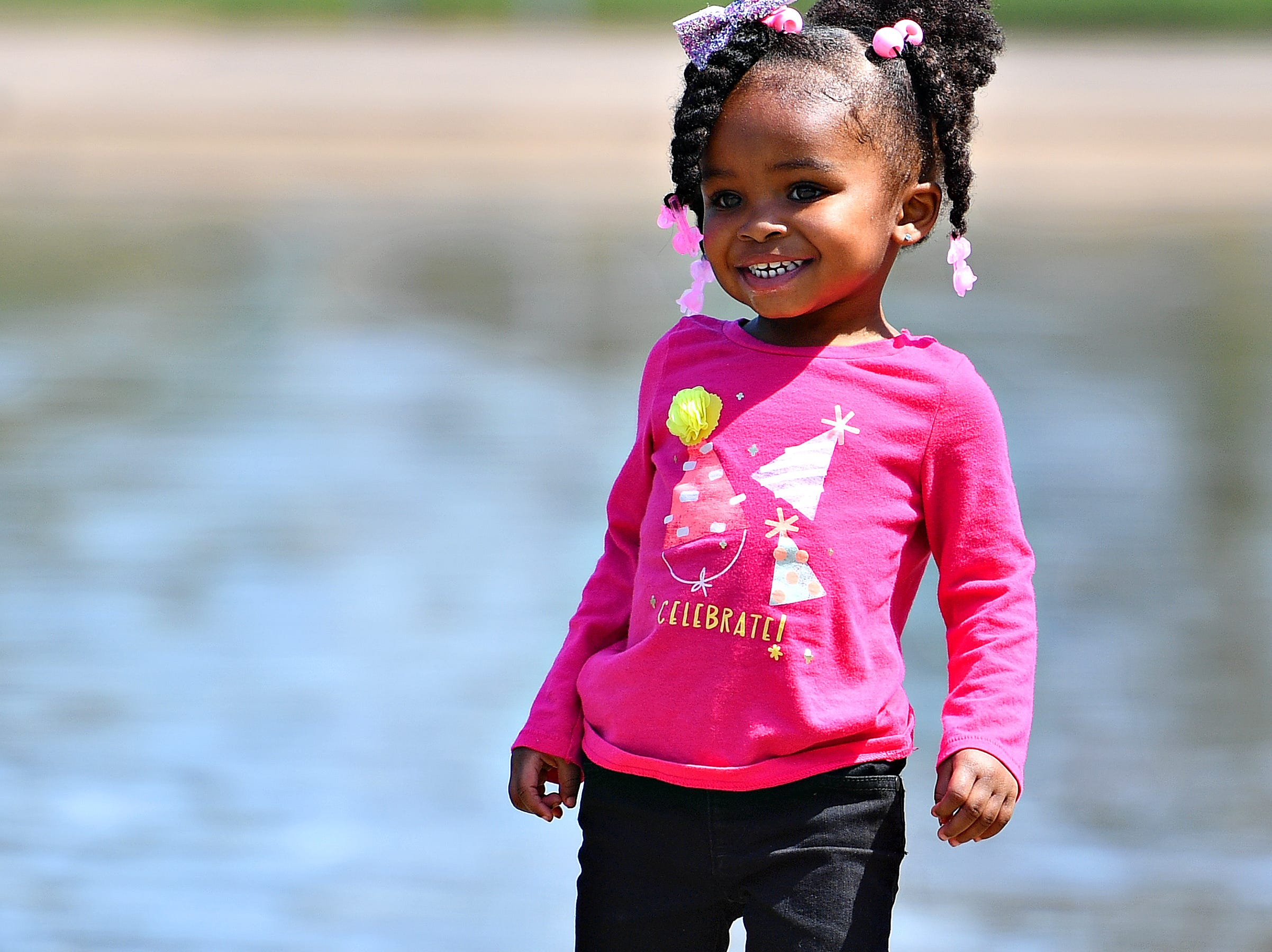 Ireyanna Rice, 2, laughs as she plays near the ducks following the 44th Annual York City Easter Egg Hunt at Kiwanis Lake in York City, Saturday, April 13, 2019. Dawn J. Sagert photo