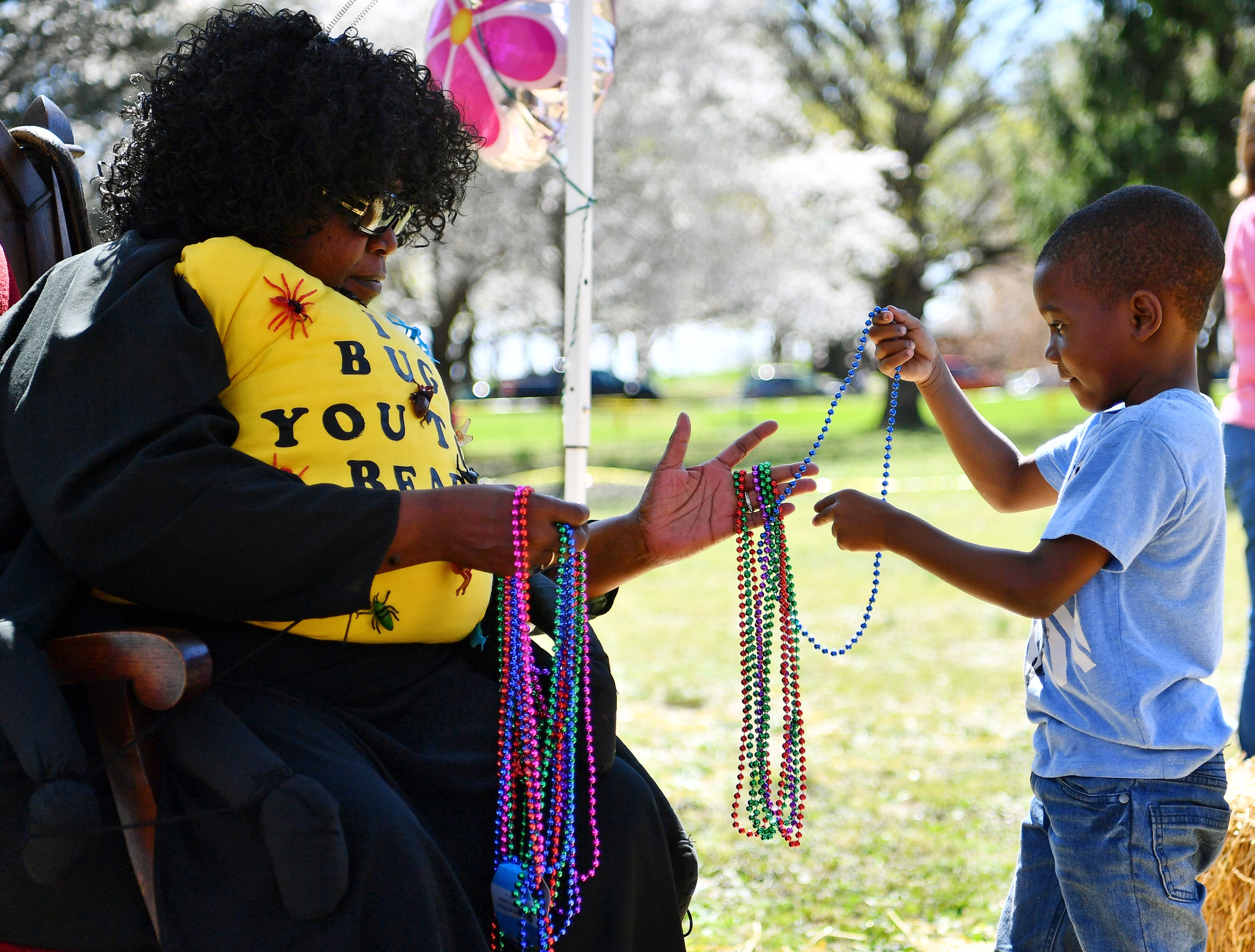 "Donna Watkins, A.K.A. ""The Reading Bug,"" of York City, hands a strand of beads to Haimere Kosh, 5, of York City, during the 44th Annual York City Easter Egg Hunt at Kiwanis Lake in York City, Saturday, April 13, 2019. Dawn J. Sagert photo"