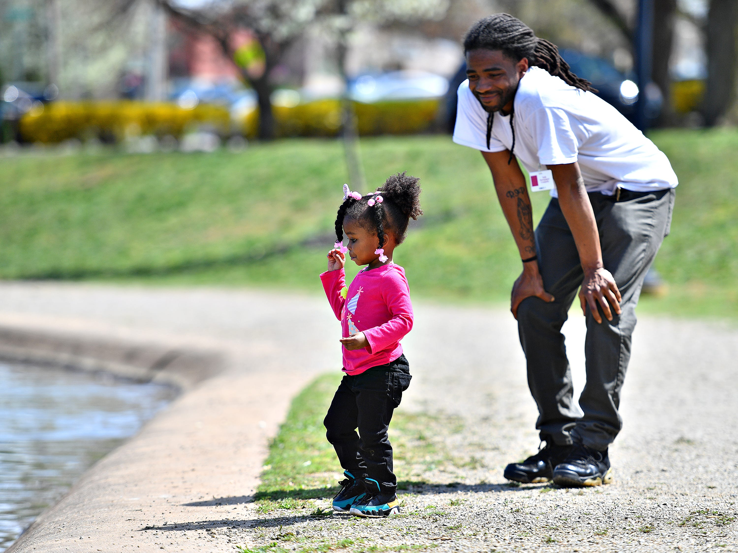 Ireyanna Rice, 2, plays near the ducks while her father Marquis Rice, of York City, looks on following the 44th Annual York City Easter Egg Hunt at Kiwanis Lake in York City, Saturday, April 13, 2019. Dawn J. Sagert photo