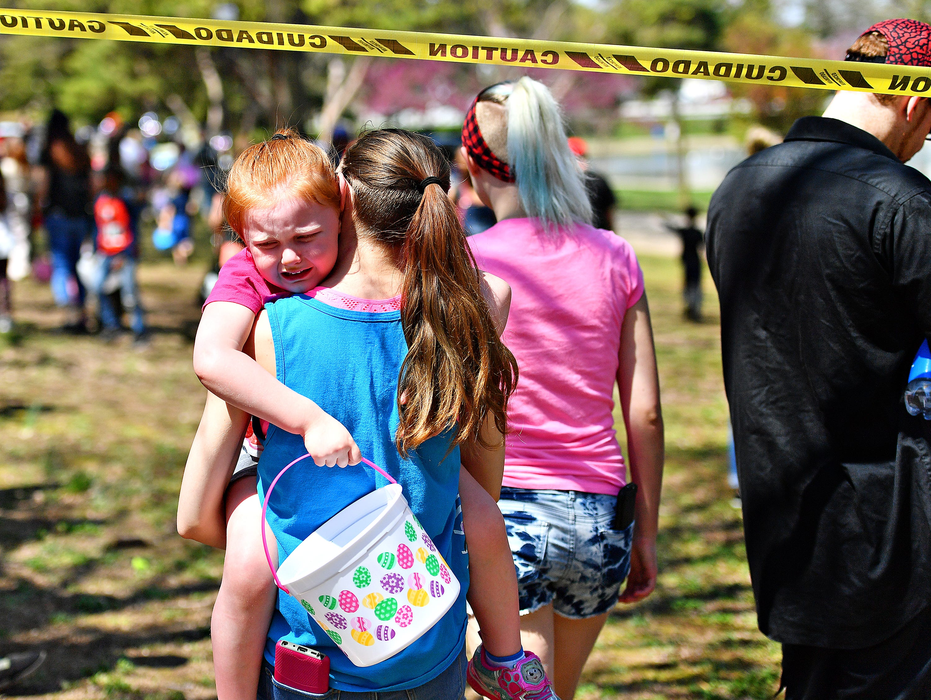 Saige Cotterman, 17, of New Salem, carries her crying sister Kaidence Giuiffre, 4, following the 44th Annual York City Easter Egg Hunt at Kiwanis Lake in York City, Saturday, April 13, 2019. Dawn J. Sagert photo