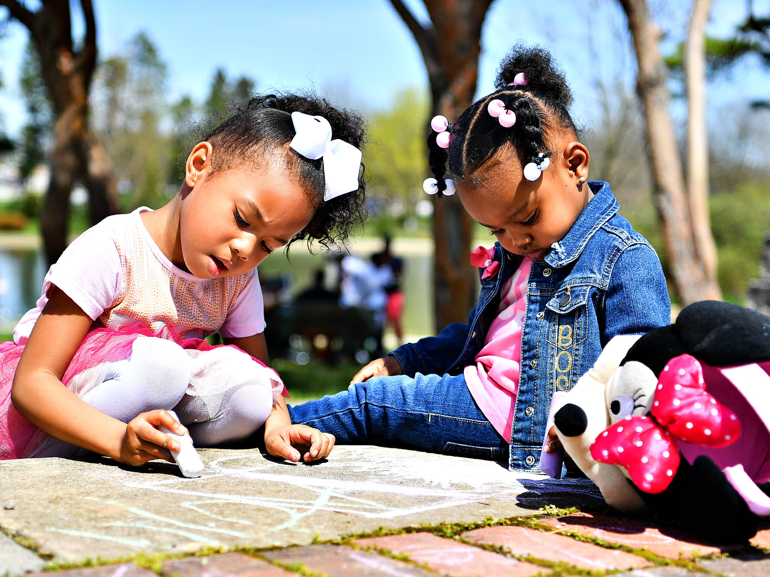Malyia Andino, 4, and Inyce Cross, 2, both of York City, draw with sidewalk chalk during the 44th Annual York City Easter Egg Hunt at Kiwanis Lake in York City, Saturday, April 13, 2019. Dawn J. Sagert photo