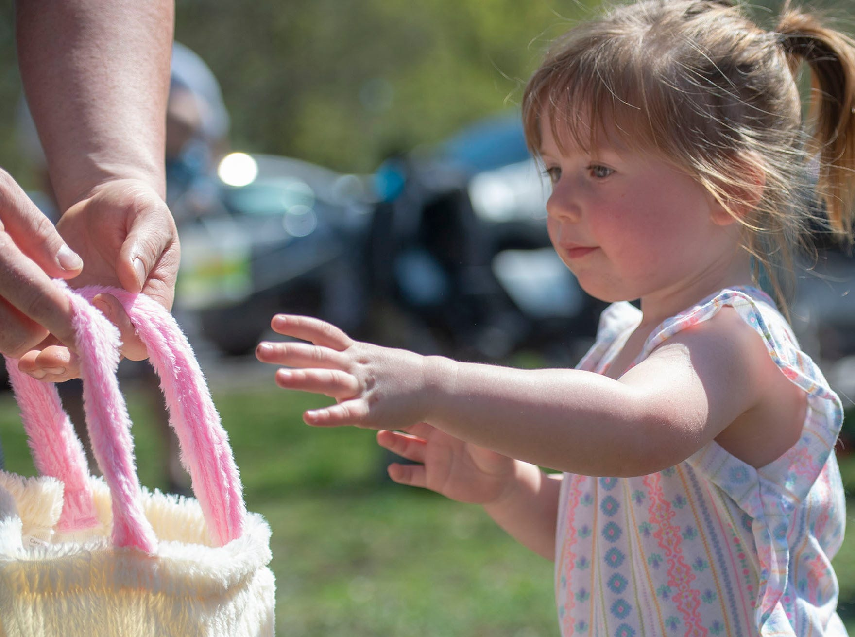 A participant reaches out to check out her goodies at the City of York's Easter Egg Hunt at Kiwanis Lake on Saturday, April 13, 2019.