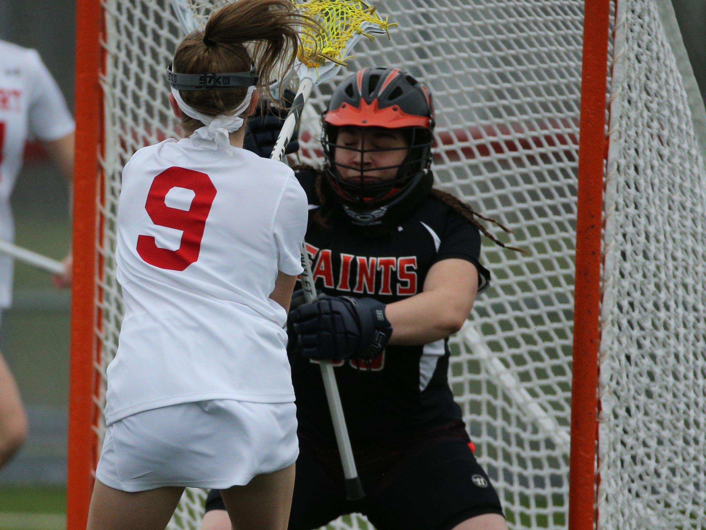 Fairport's Meghan McLachlan finds the net by shooting over Churchville goalie Bryanna Phillips.