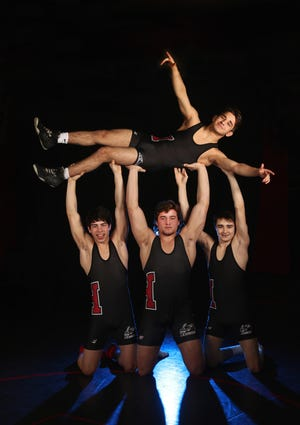 Hilton continues a wrestling legacy with four state champions, from left are Ryan Burgos, Sammy DePrez and Gregor McNeil holding up  teammate Greg Diakomihalis,
