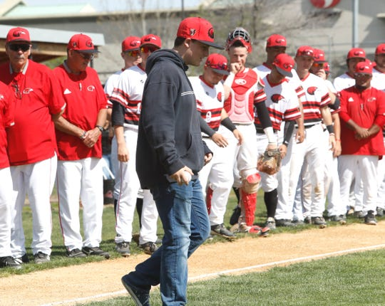 Caleb Stoke, the 14-year-old son of fallen Redding firefighter Jeremy Stoke, walks to the mound Saturday morning to throw out the first pitch of the Simpson University baseball game against Marymount California University.
