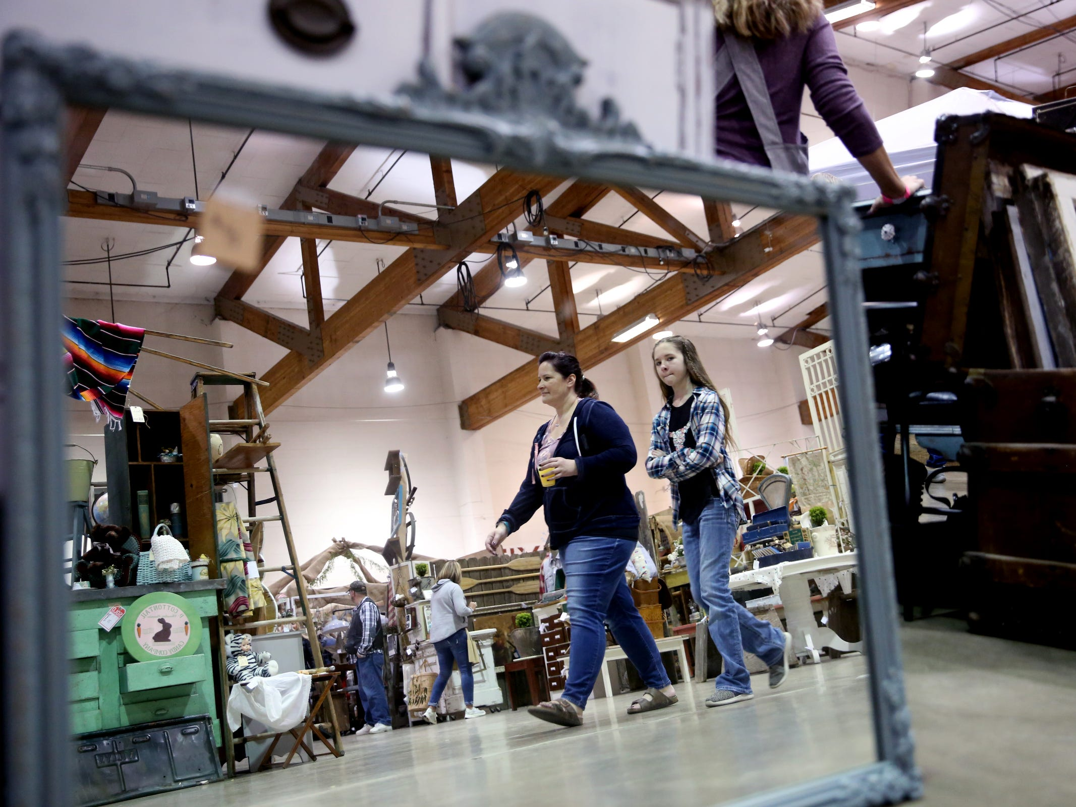 Shoppers are reflected in a mirror available during The Great Junk Hunt, a traveling vintage market, at the Oregon State Fairgrounds in Salem on April 13, 2019.