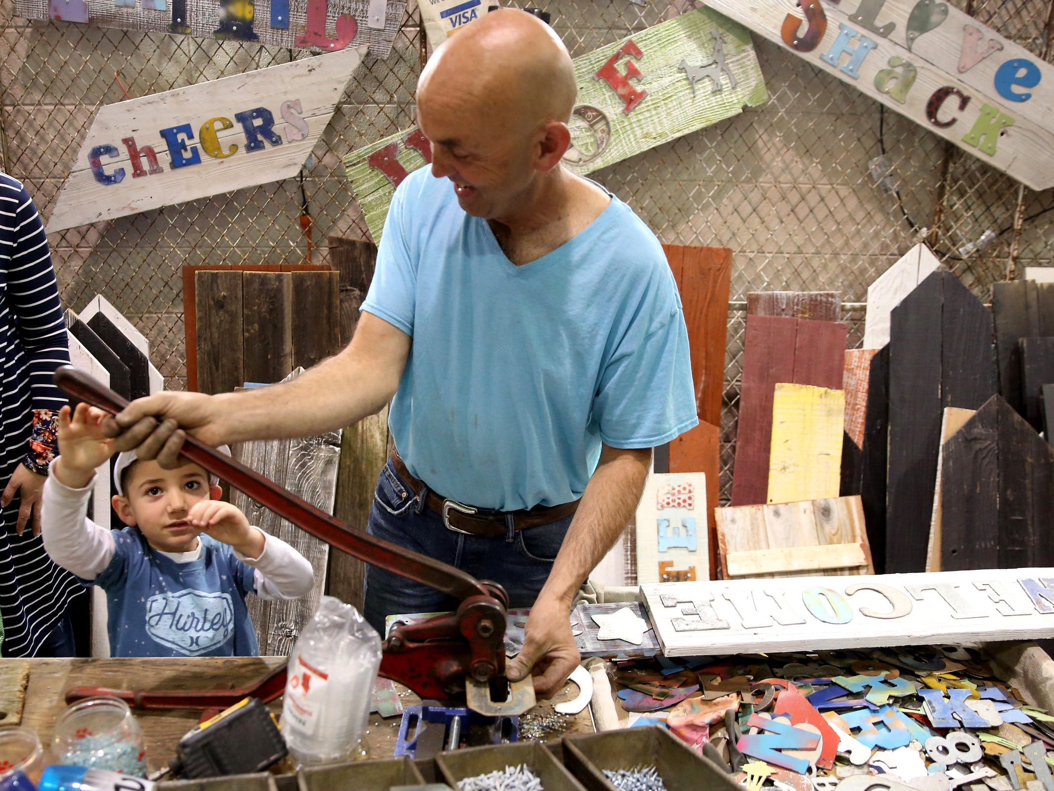 Garrett Maskal, 5, of Keizer, helps Fred Grandy punch a hole in a piece of metal for a custom sign during The Great Junk Hunt, a traveling vintage market, at the Oregon State Fairgrounds in Salem on April 13, 2019.